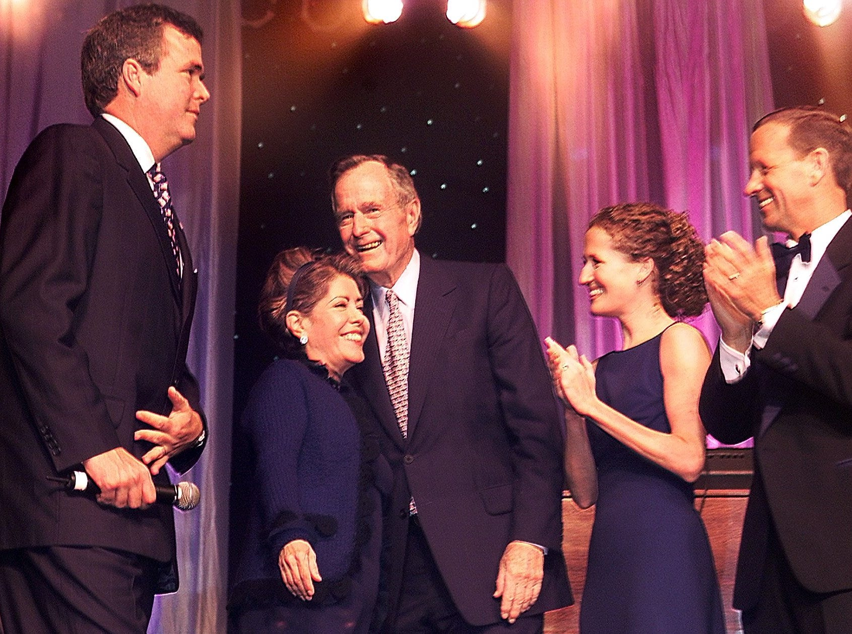 Former President George H. W. Bush (center) hugs son Jeb's wife , as they are joined by (from left) Jeb's son George P. Bush, and (right) Courtney and her new husband, Florida's lieutenant governor Frank Brogan at the Inauguration Party.