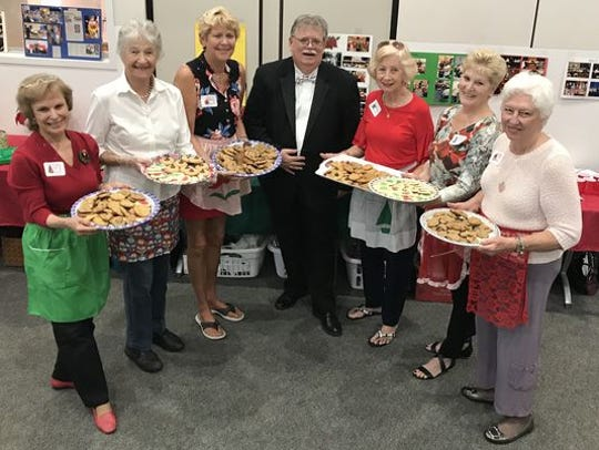 Yes, there will be cookies. Jim LeBon, director of the Stuart Community Concert Band, is posing in this photo with the Palm City Cookie Ladies.