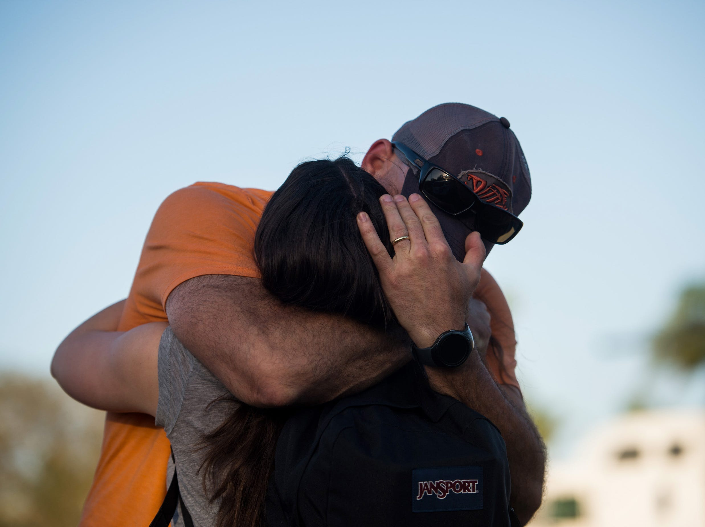 A father embraces his daughter Wednesday, Feb. 14, 2018, at University Drive and Holmberg Road, where students reunited with family members after a mass shooting at Marjory Stoneman Douglas High School in Parkland.