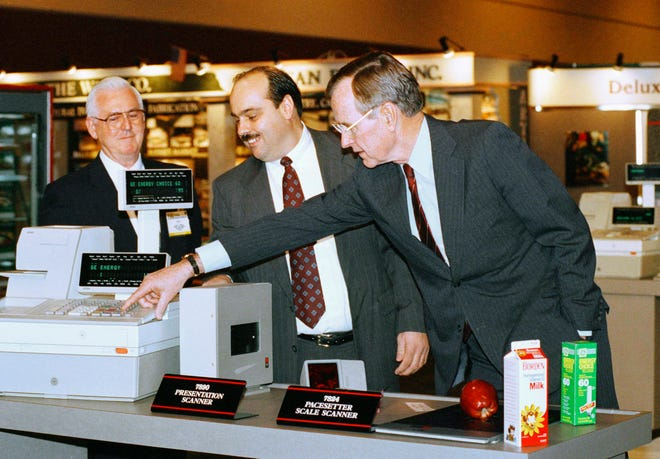 In this Feb. 4, 1992, file photo, President George H. W. Bush, right, pushes the keys on a new high technology cash register under the watchful eyes of Leo Hardy, left, and Bob Graham, center, during a visit to the National Grocers Association trade show in Orlando, Fla.
