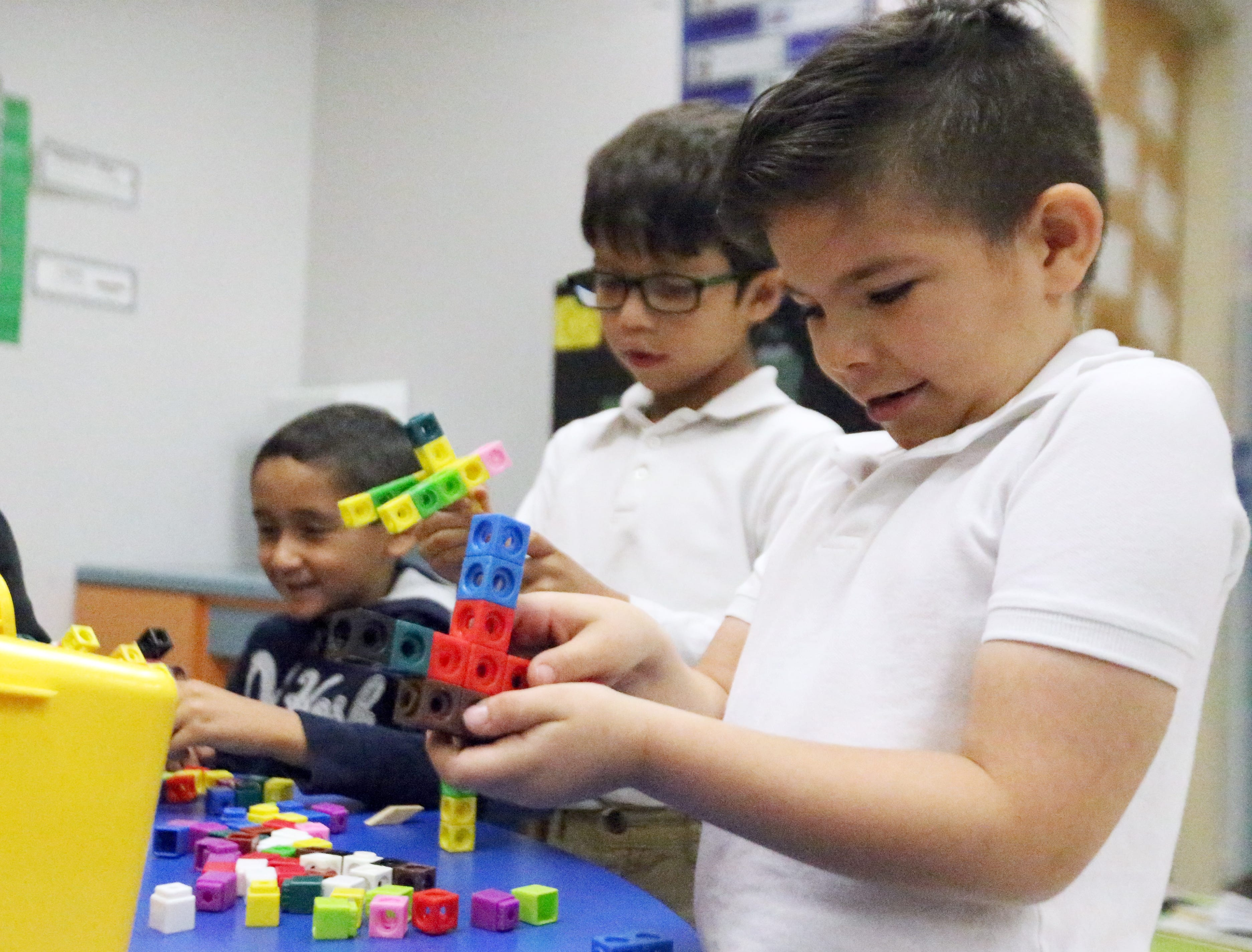 Christopher Robles, right, works with classmates in building 'robot zombies' from building cubes during an activity time in Zelene Blancas' first grade bilingual class at Dr. Sue Shook Elementary School in far East El Paso.