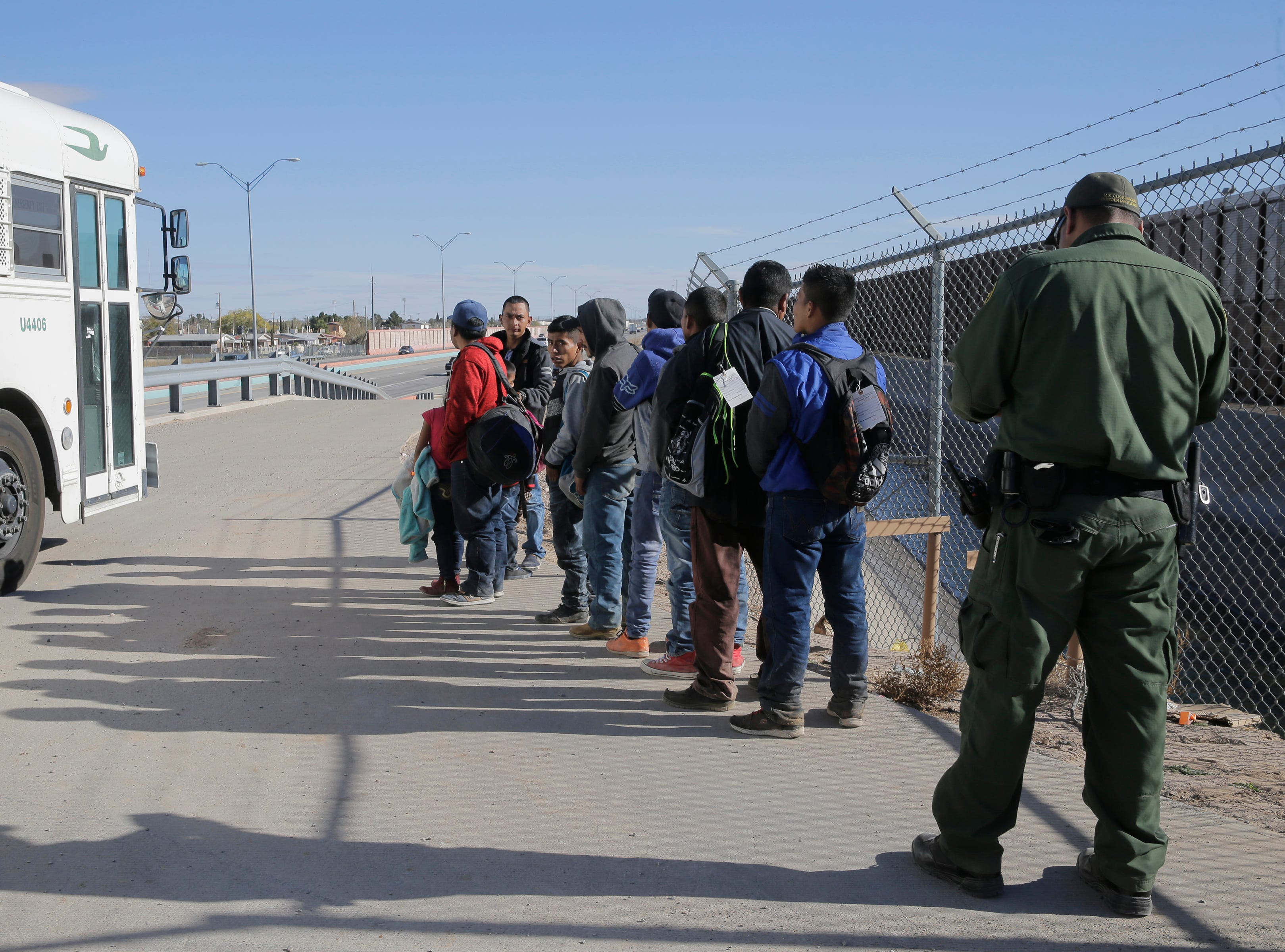 A large group of migrants were detained by Border Patrol Monday at the border fence along the Border Highway near Fonseca. Here the final group of immigrants that were detained wait to board a Border Patrol bus for transport to the El Paso Border Patrol detention facility.
