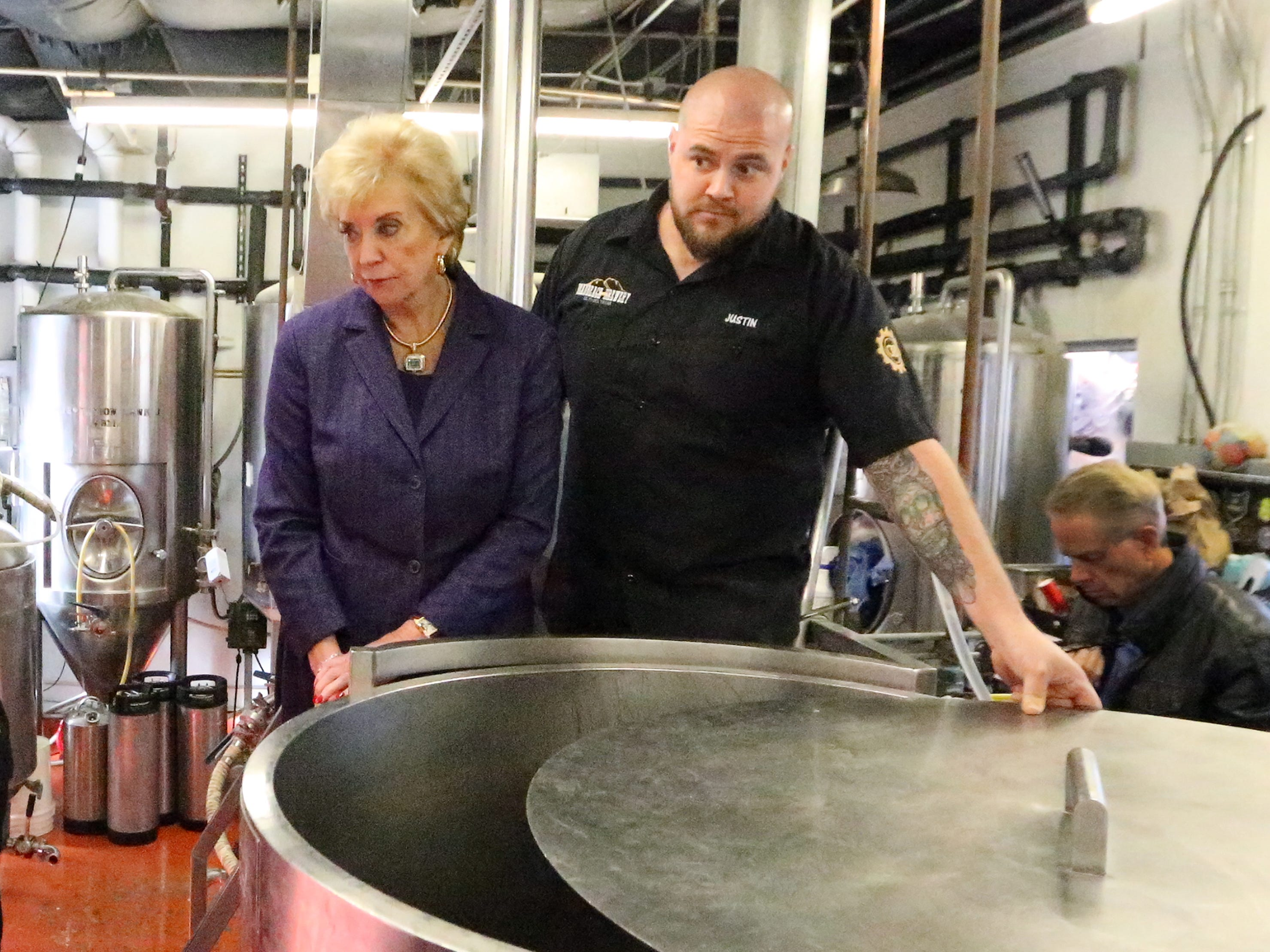 U.S. Small Business Administration director Linda McMahon, left, is shown a piece of beer making equipment by Justin Ordoñez, co-owner of DeadBeach Brewery at 406 Durango Street during a visit to El Paso Tuesday.
