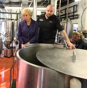 U.S. Small Business Administration director Linda McMahon, left, is shown a piece of beer making equipment by Justin Ordoñez, co-owner of DeadBeach Brewery at 406 Durango St. during a visit to El Paso.