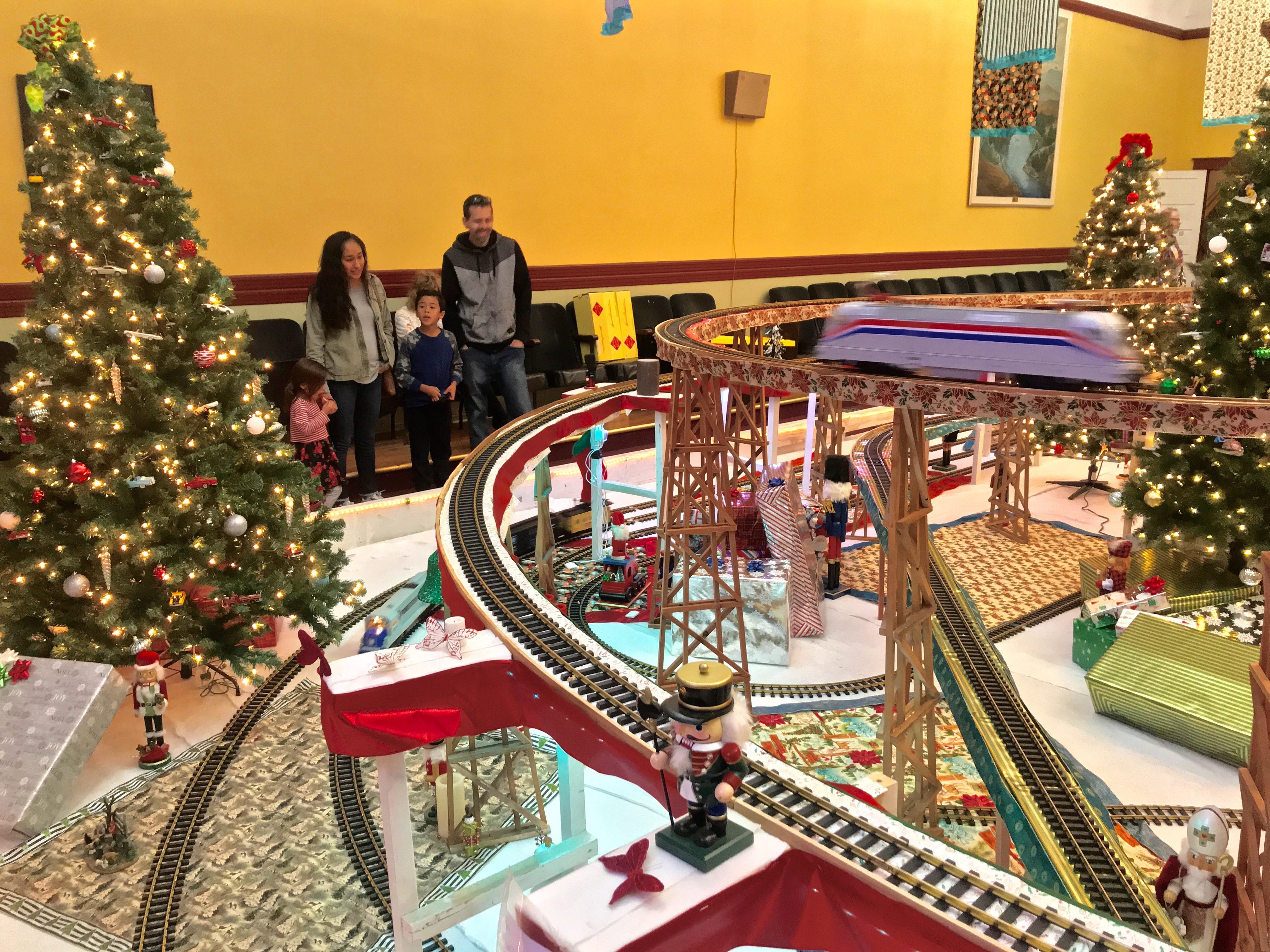 A family watches toy trains at the Odd Fellows Christmas train display in Santa Paula.