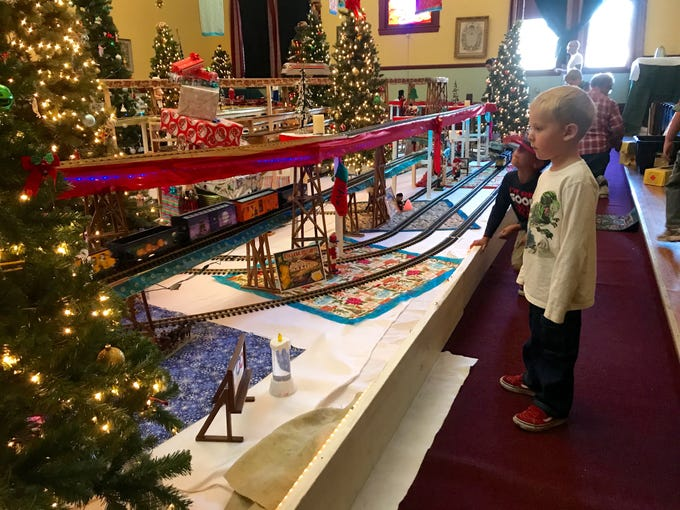 Zachary Benigar, of Santa Paula, watches toy trains trundle past him at the Odd Fellows Christmas train display.