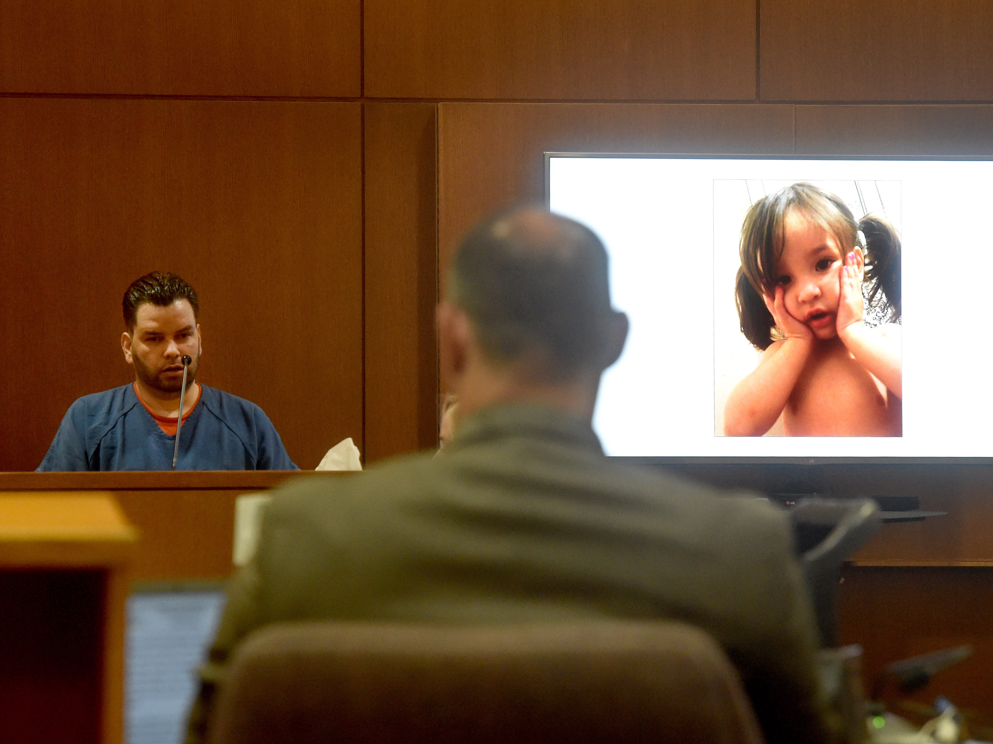 Omar Lopez, 33, of Oxnard, testifies during the trial of Mayra Chavez on Dec. 3, 2018, in Ventura County Superior Court.  Chavez is charged with second-degree murder in the death of their daughter Kimberly. A photo of a young Kimberly was projected on a screen next to the witness stand.