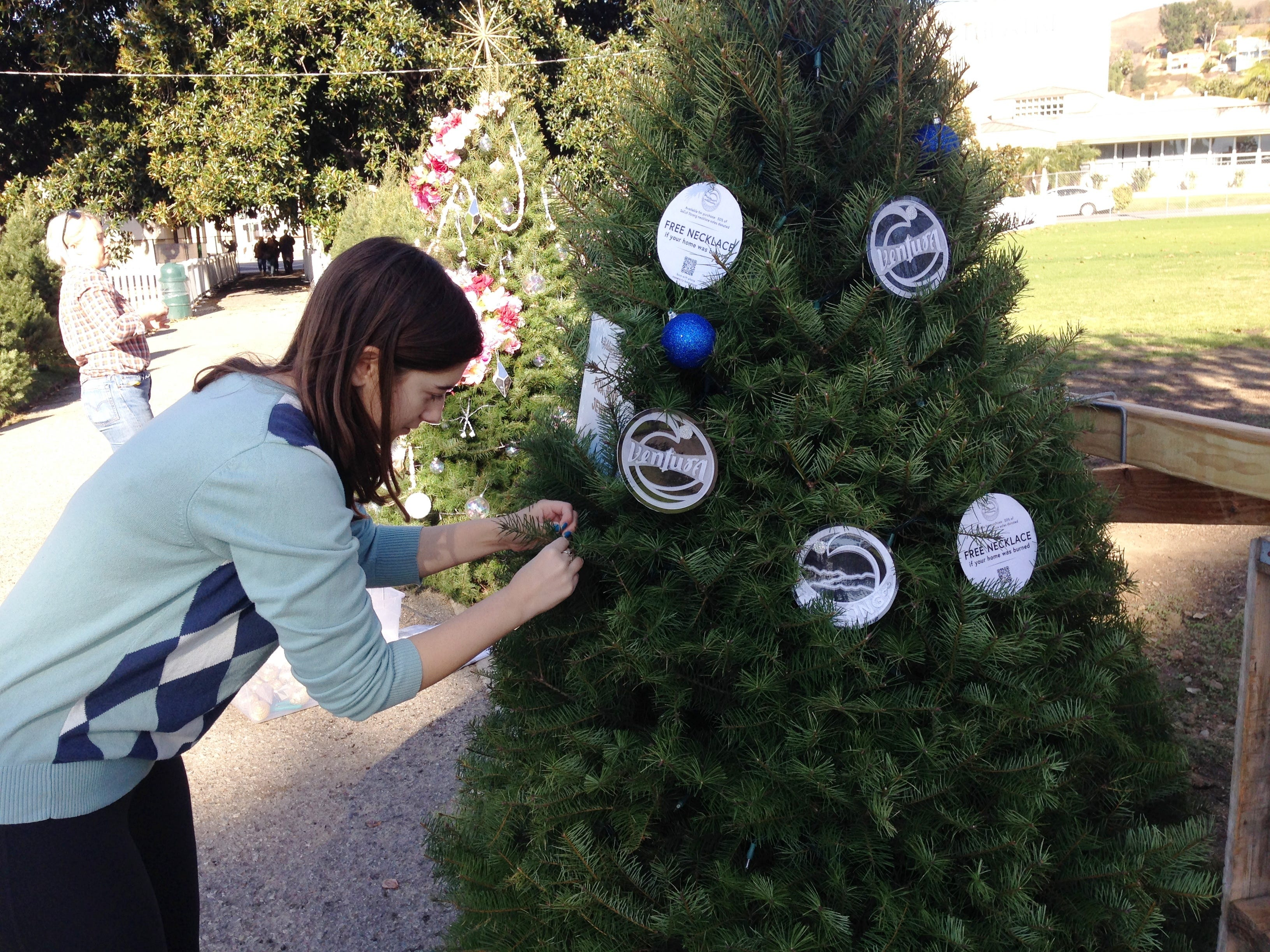 Charlotte Fox decorates a Christmas tree for Holidays at the Plaza, an event at Plaza Park in Ventura running Dec. 7 through Jan. 2 that will showcase more than 100 elaborately decorated trees.