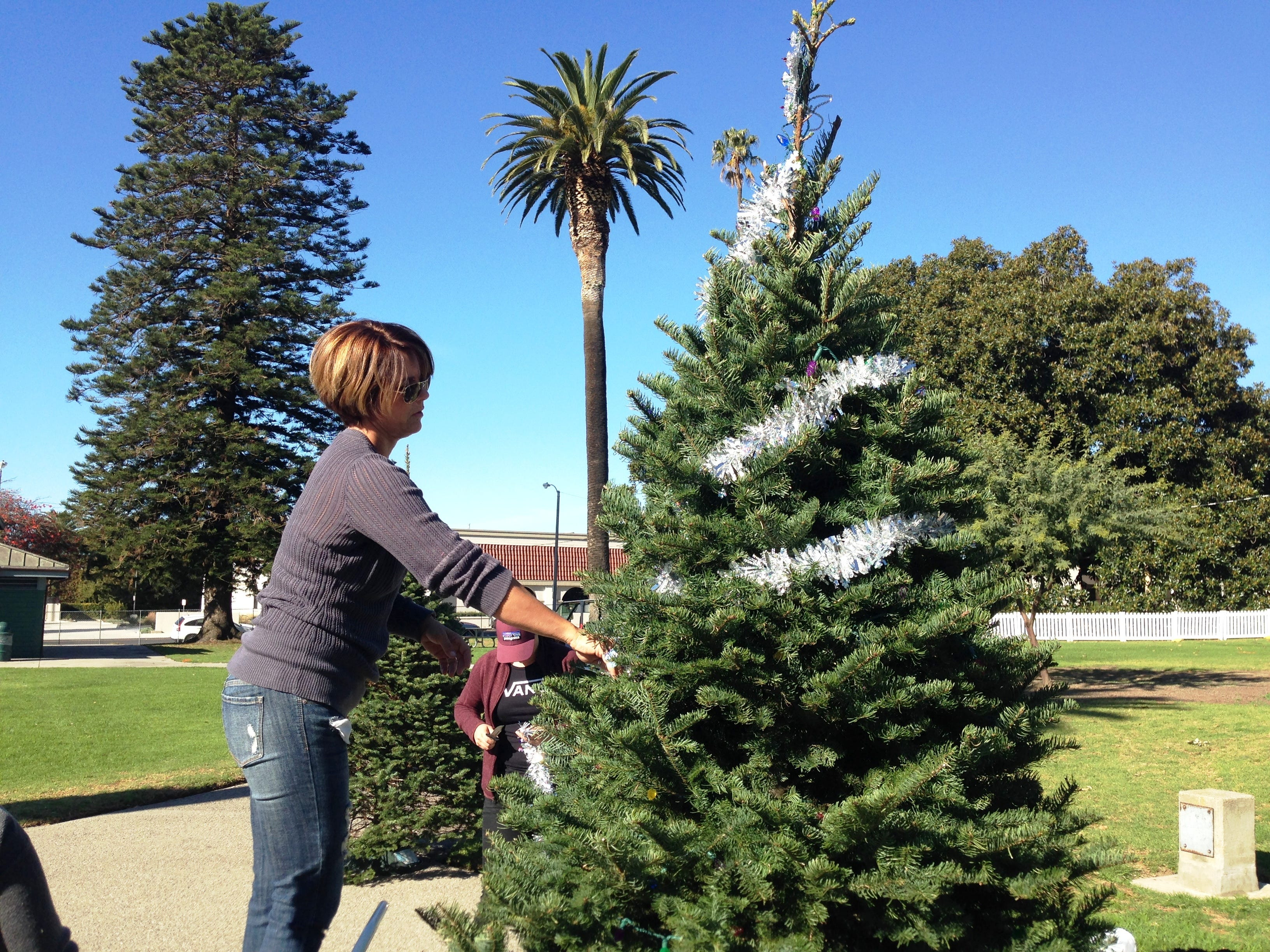 Diana Shillington decorates a Christmas tree sponsored by Las Posas Children's Center for Holidays at the Plaza, an event at Plaza Park in Ventura running Dec. 7 through Jan. 2 at Plaza Park in Ventura. The event showcases more than 100 elaborately decorated trees, as well as several holiday-themed activities.