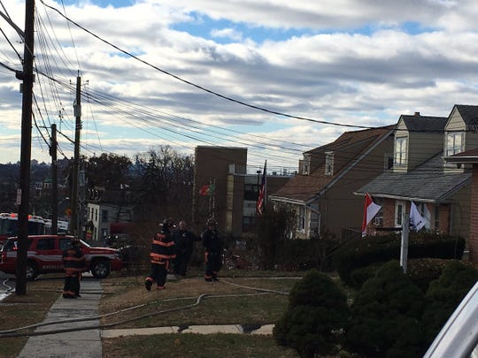 Firefighters at the scene of a basement apartment fire at 131 Park Ave. in Yonkers, onTuesday. Firefighters pulled a woman from the smoky apartment, but she later died.