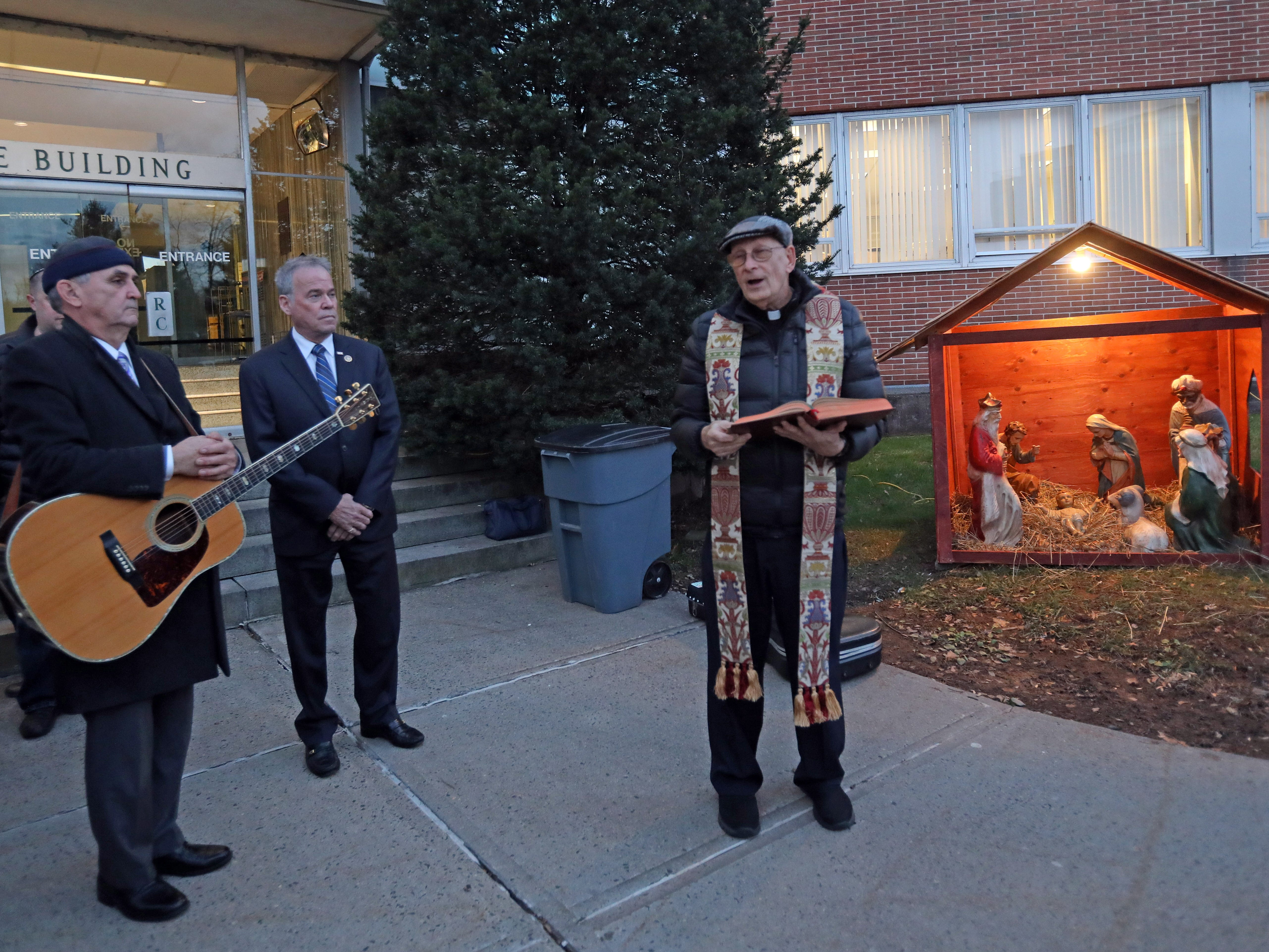Father Tom Ruekert, center, of Marian Shrine Church of Stony Point says a prayer during The Blessing of the Nativity Creche in front of the Rockland County Office Building in New City Dec. 3, 2018.