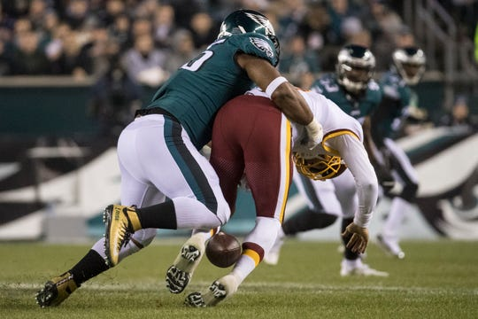 Washington's Mark Sanchez fumbles the ball as he is tackled by the Eagles' Brandon Graham Monday night.