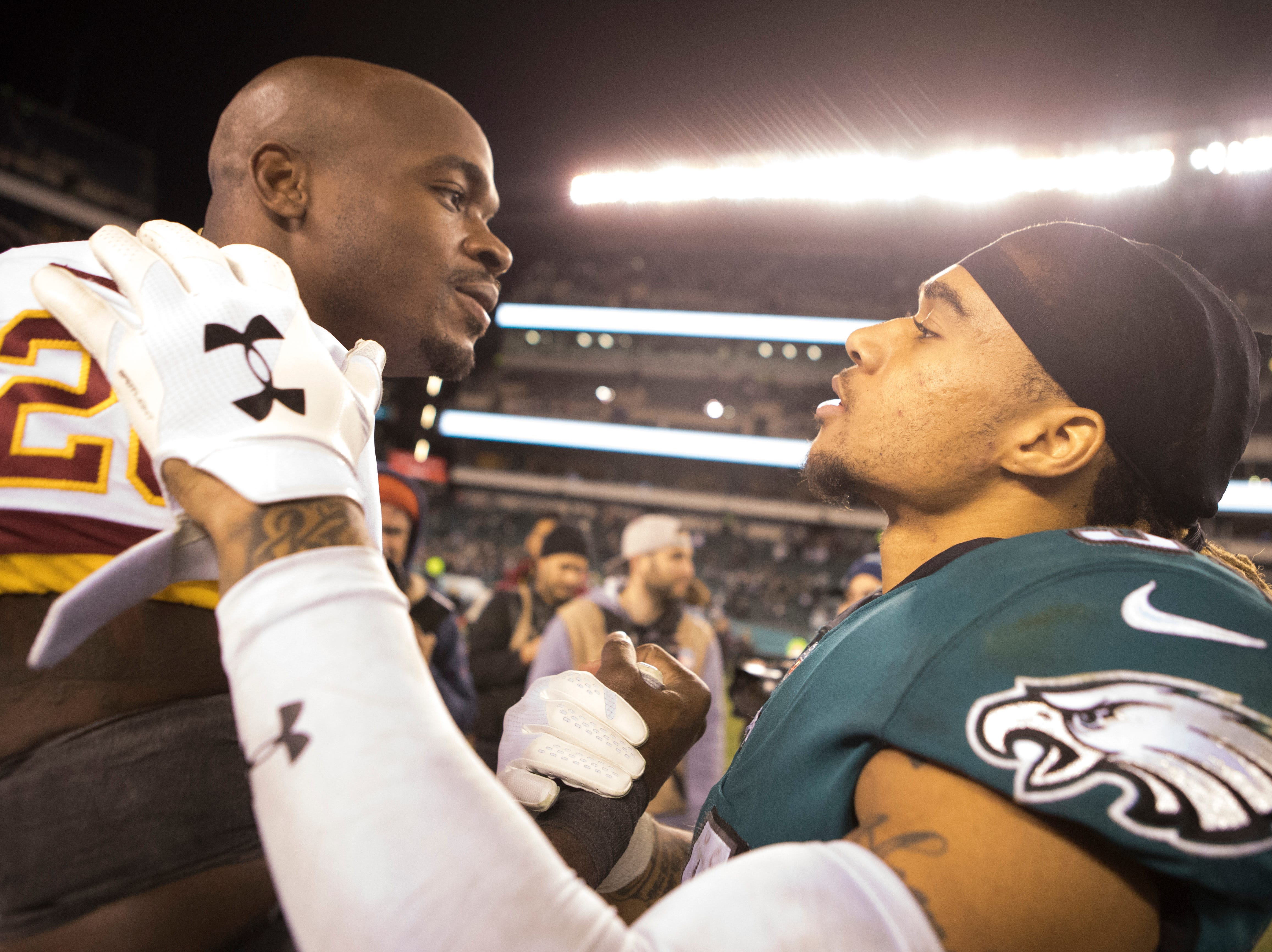 Eagles' Cre'Von LeBlanc (34) visits with Washington's Adrian Peterson (26) after the game Monday night.