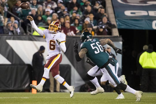 Washington's Mark Sanchez (6) throws under pressure by Philadelphia's Chris Long Monday night.