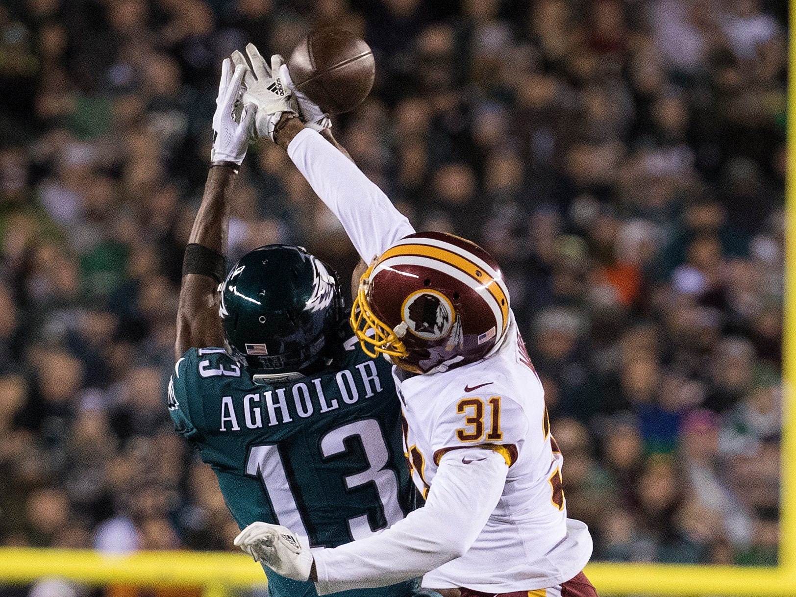 Eagles' Nelson Agholor (13) battles with Washington's Fabian Moreau (31) for a reception Monday night.