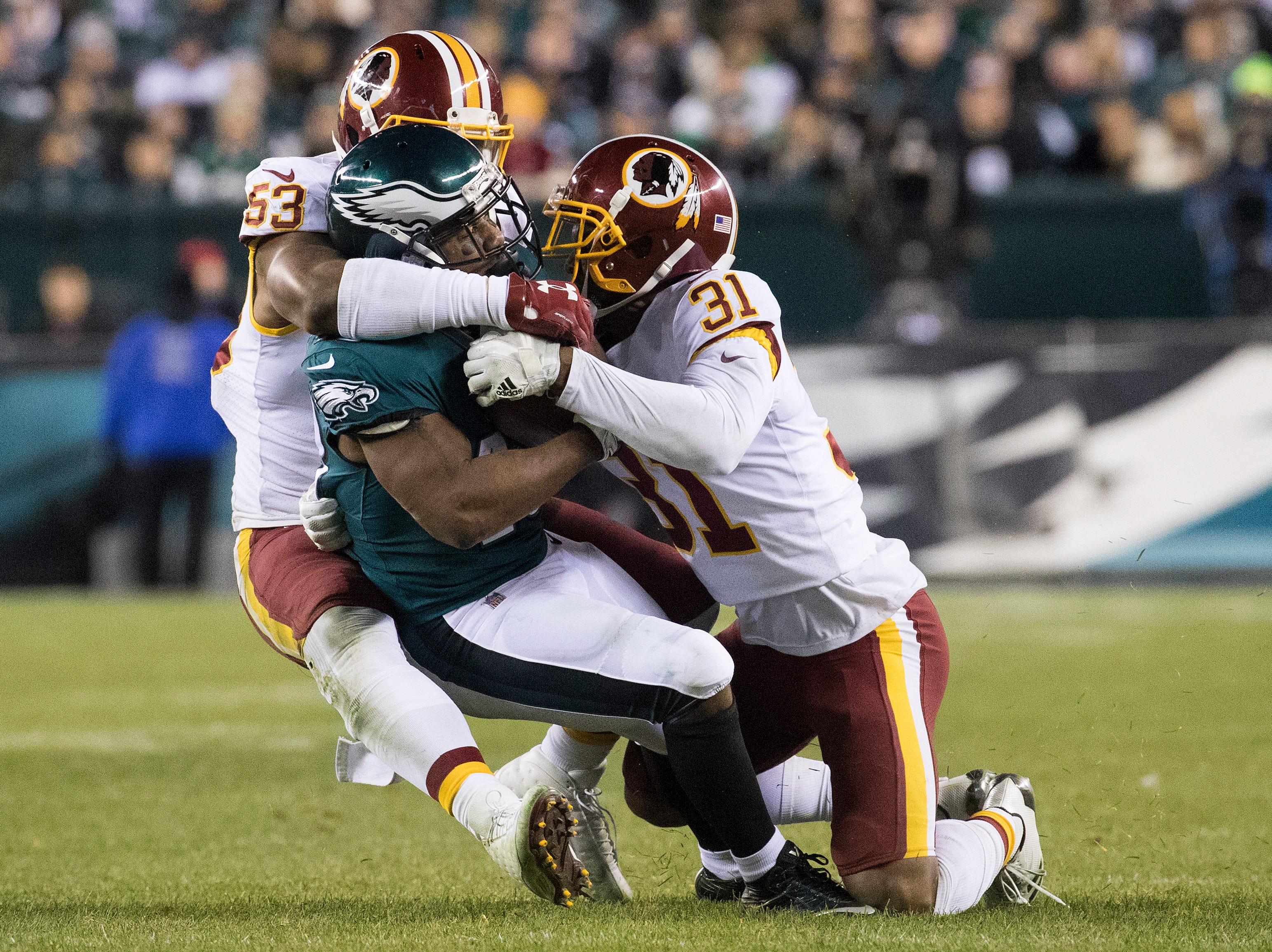 Washington's Fabian Moreau (31) and Zach Brown (53) wrap up the Eagles' Darren Sproles (43) Monday night.