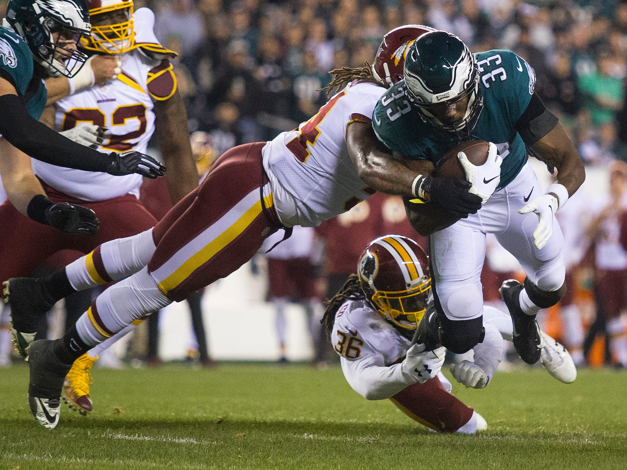 Eagles' Josh Adams (33) is brought down by the Redskins defense Monday night at Lincoln Financial Field.