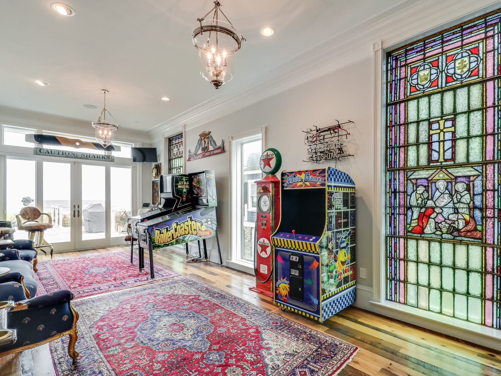 The colorful game room at 18 Ocean Drive in North Beach includes video games and a stained glass panel.
