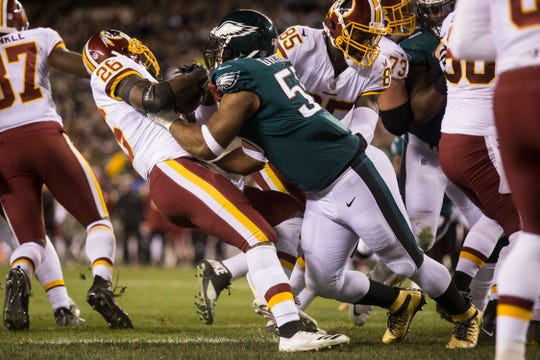 Eagles' Brandon Graham (55) brings down Washington's Adrian Peterson (26) Monday night.