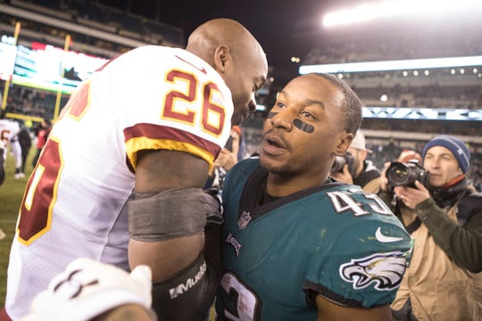 Eagles' Darren Sproles (43) hugs Washington's Adrian Peterson (26) after the game Monday night.