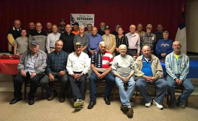 Several veterans recently received quilts from the Pieceable Quilters Guild. Sitting are Bill Kittle, Dave Abele, Kenny Evec, Marvin Stoneburner, Ron Ball, Bill Agin and Charles Fisher. Standing in front are Danielle Gray, Daniel Beebe, Terry Ludman, Bob Jones, Vickie Stamm, Joe Mincher, John Tignor, Cindy Day, Robert John Smith, Ron Chapman and Sandra Scott. In the back are Terry Clark, James Sharrer, Dave Lyons, Tony Adams, Glenden Bennett, Stephen House, James Pandy, Bill Ferrell, Richard Patterson and Jim Peters
