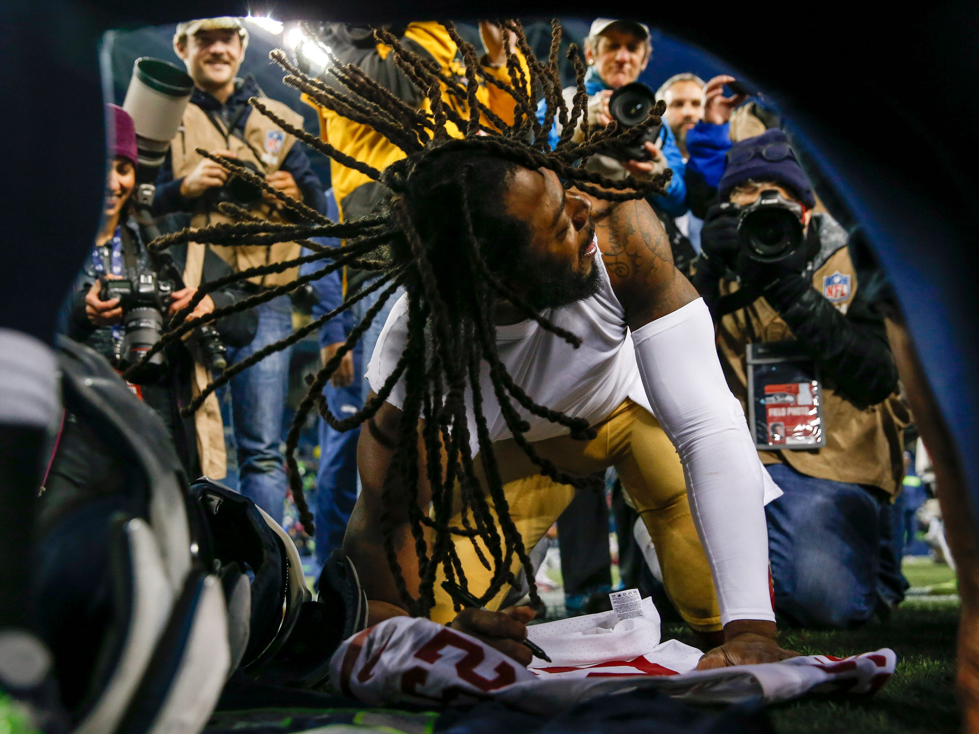 Week 13: San Francisco 49ers cornerback Richard Sherman autographs his jersey  following a 43-16 Seattle Seahawks victory at CenturyLink Field.