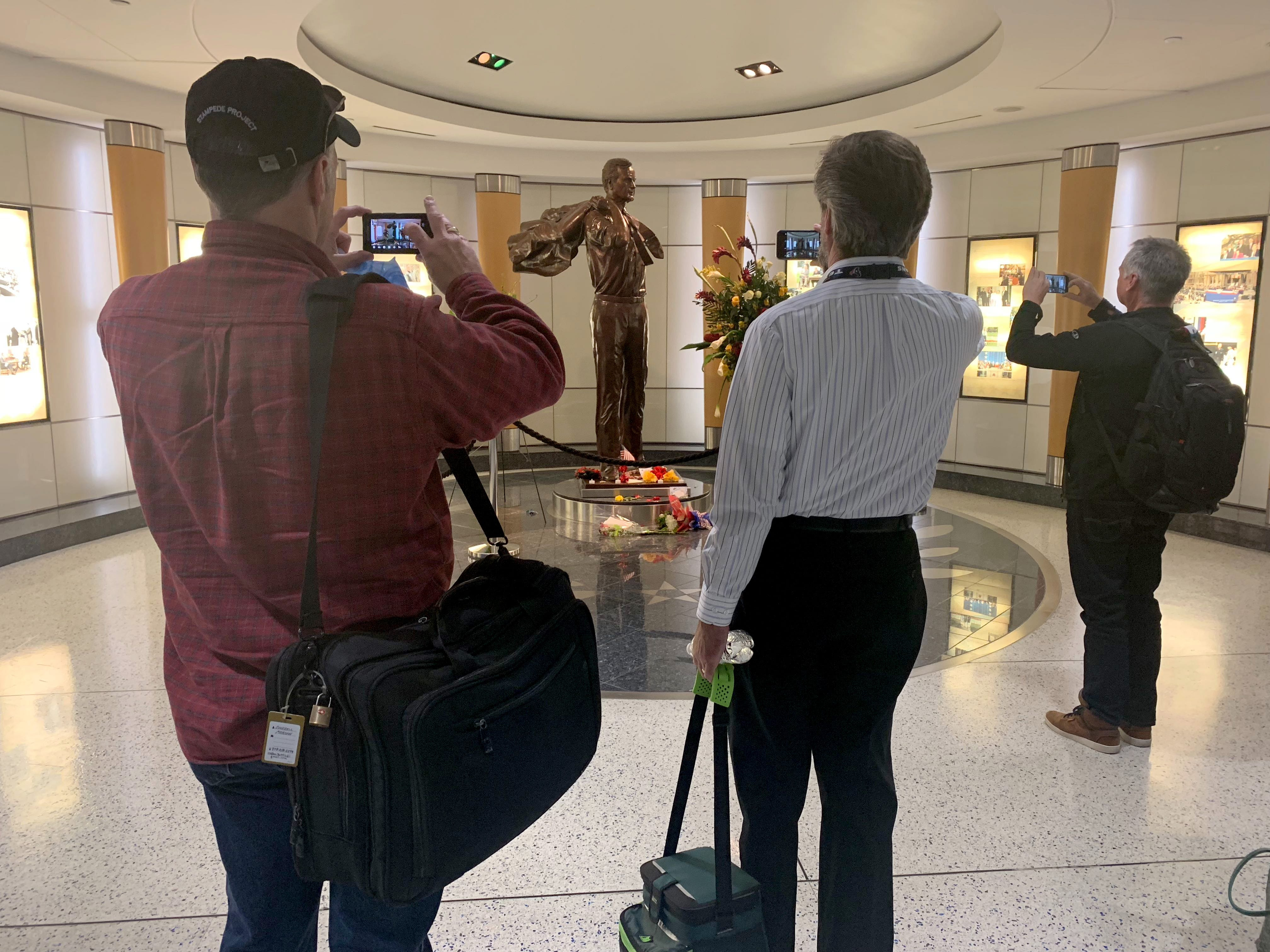 People stop to take a photo of a statue of George H.W. Bush at the George Bush Intercontinental Airport in Houston, TX., Dec. 4, 2018.  Others have left flowers.