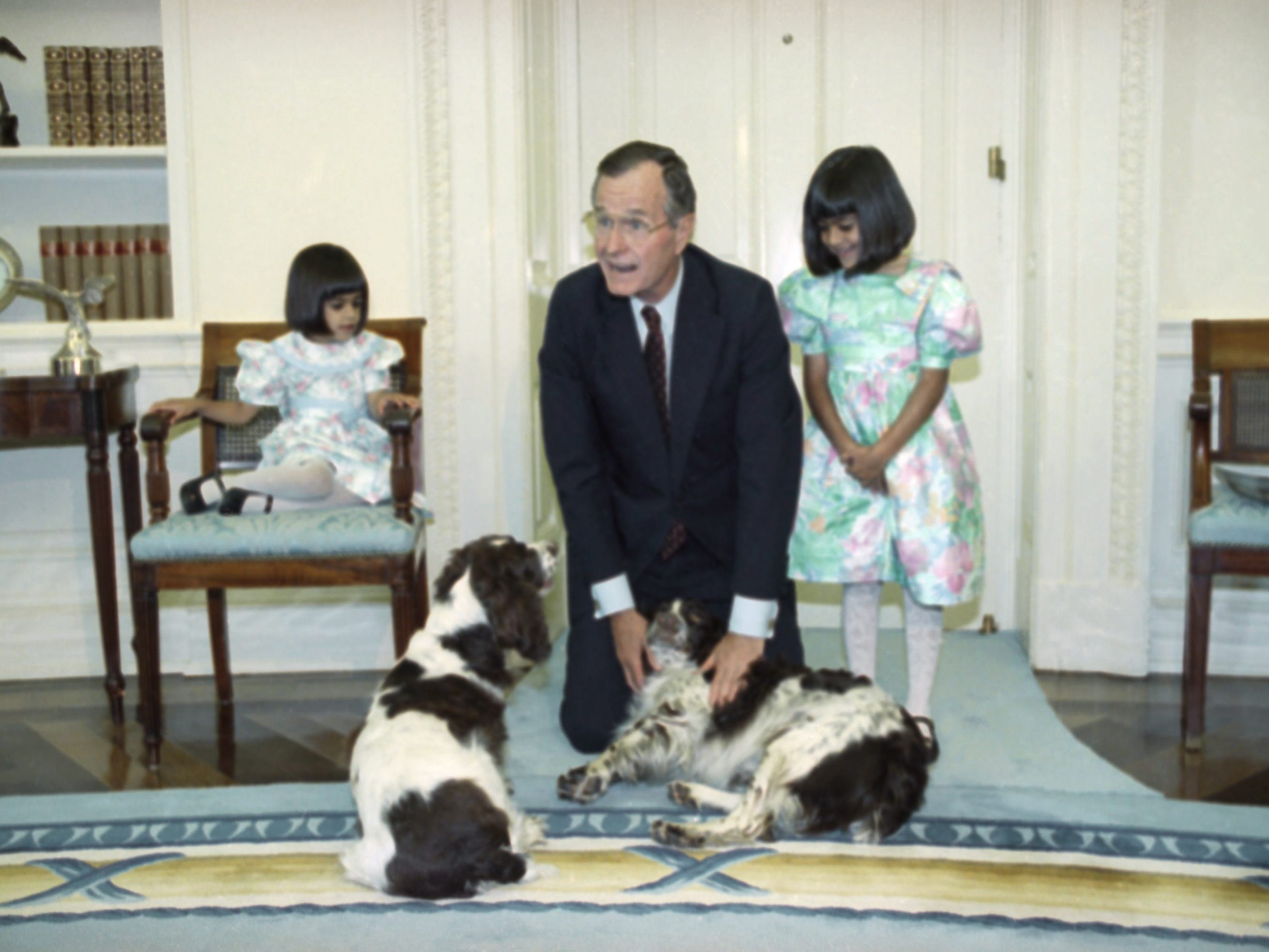President George Bush gets down on his knees to show off his dogs, Millie and Ranger, May 2, 1991 in the White House Oval Office to his guests at Washington, Neera Khurana, age 4, and her sister Sonia, age 6, right, who is the 1991 poster child for Better Hearing and Speech Month. Sonia attends the Houston School for Deaf Children in Texas. (AP Photo/Barry Thumma)