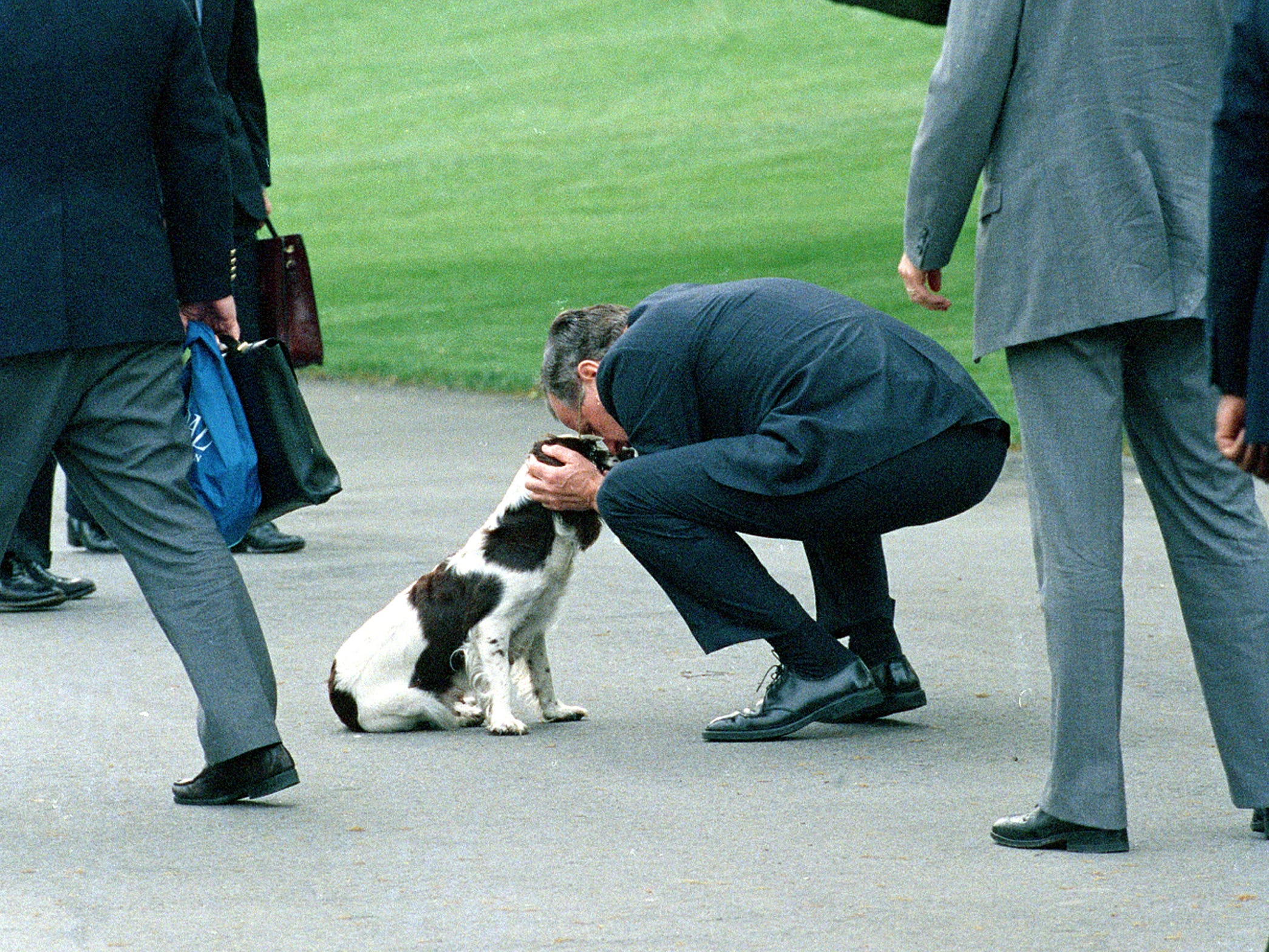 U.S. President George Bush kneels to greet his dog, Millie, upon arriving back from a four-day cross country trip at the White House in Washington, D.C., Thursday, April 27, 1989.  (AP Photo/Doug Mills)