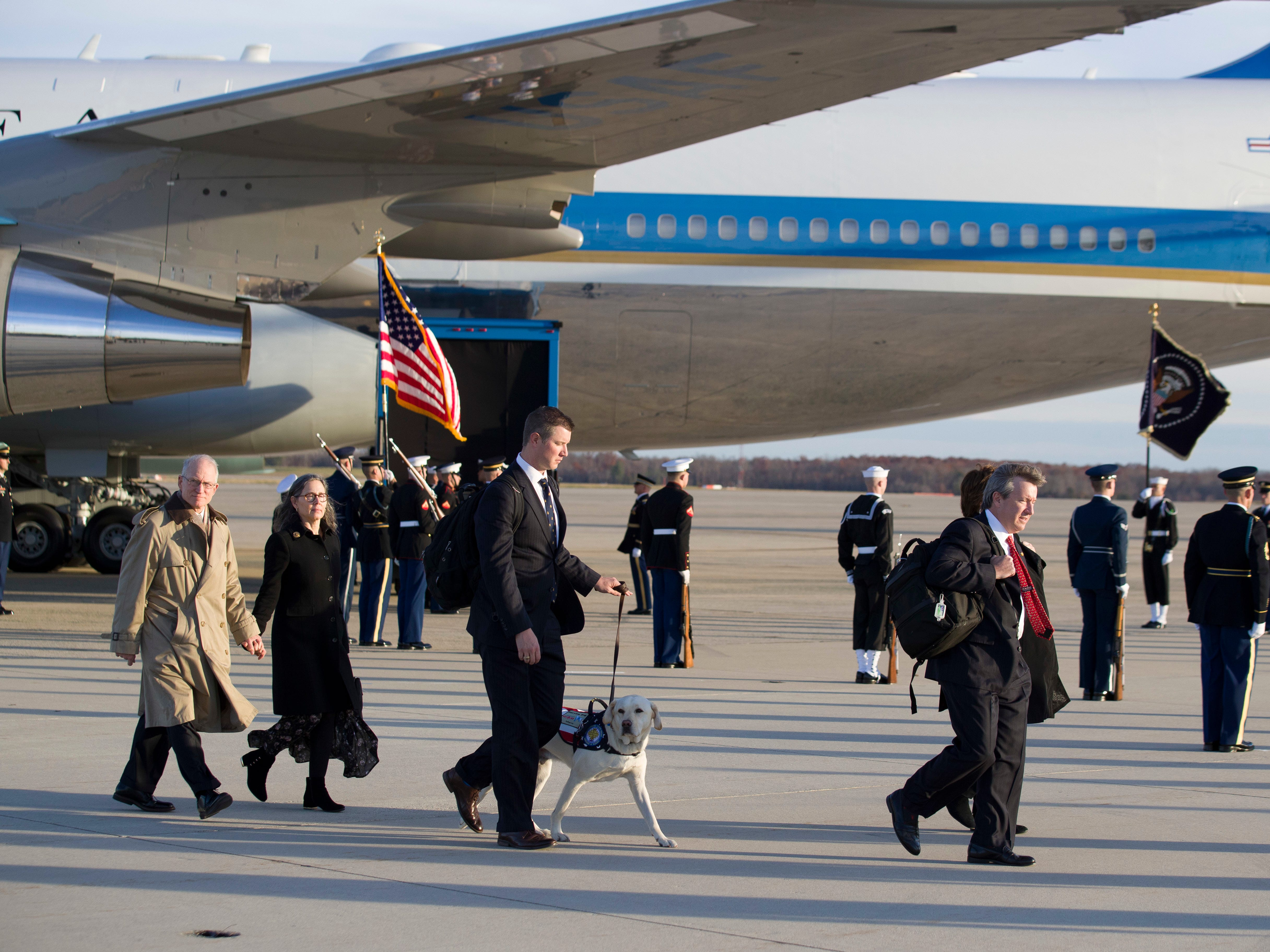 Family members, with Sully, arrive before the flag-draped casket of former President George H.W. Bush is carried by a joint services military honor guard to the hearse, Monday, Dec. 3, 2018, at Andrews Air Force Base, Md. (AP Photo/Alex Brandon, Pool) ORG XMIT: MDAB106