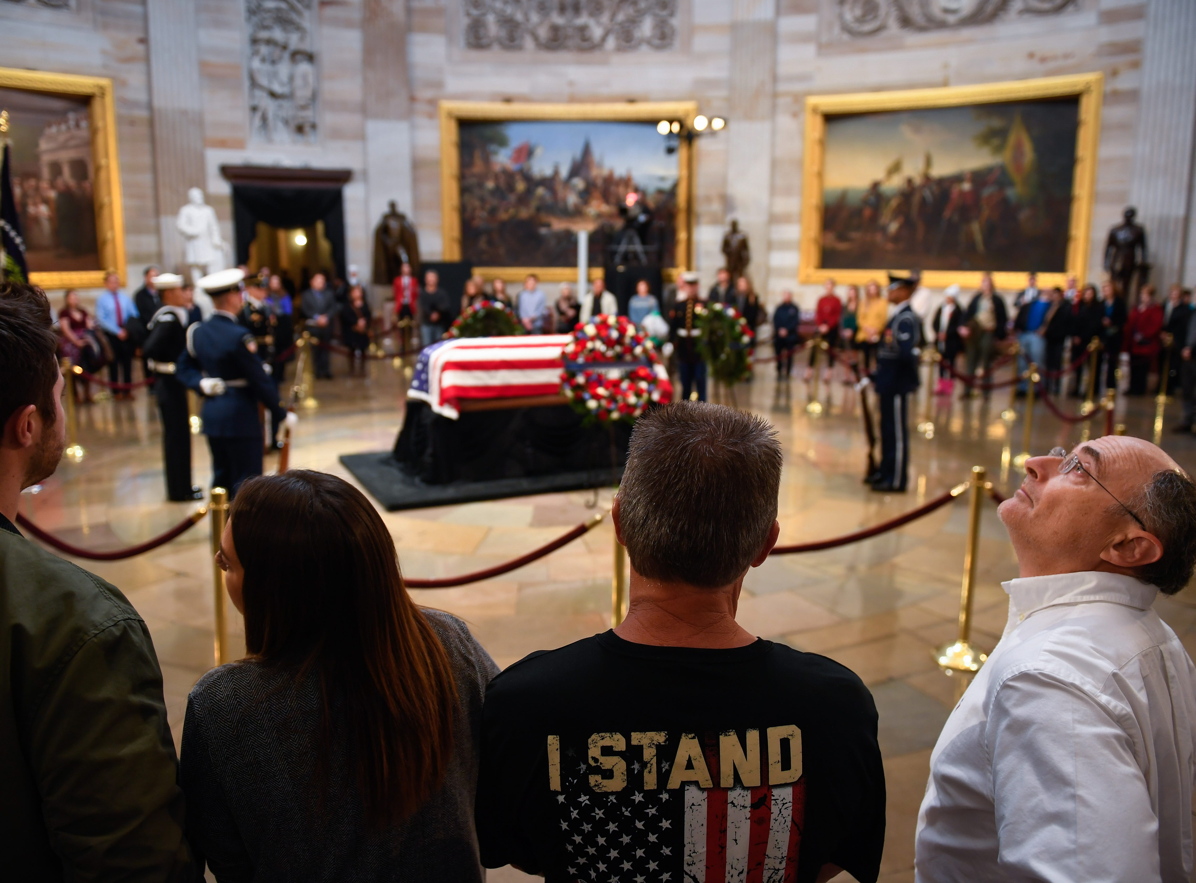 Visitors take in the scene at the the Capitol Rotunda and pay respects to President George H.W. Bush as he lies in state, Tuesday.