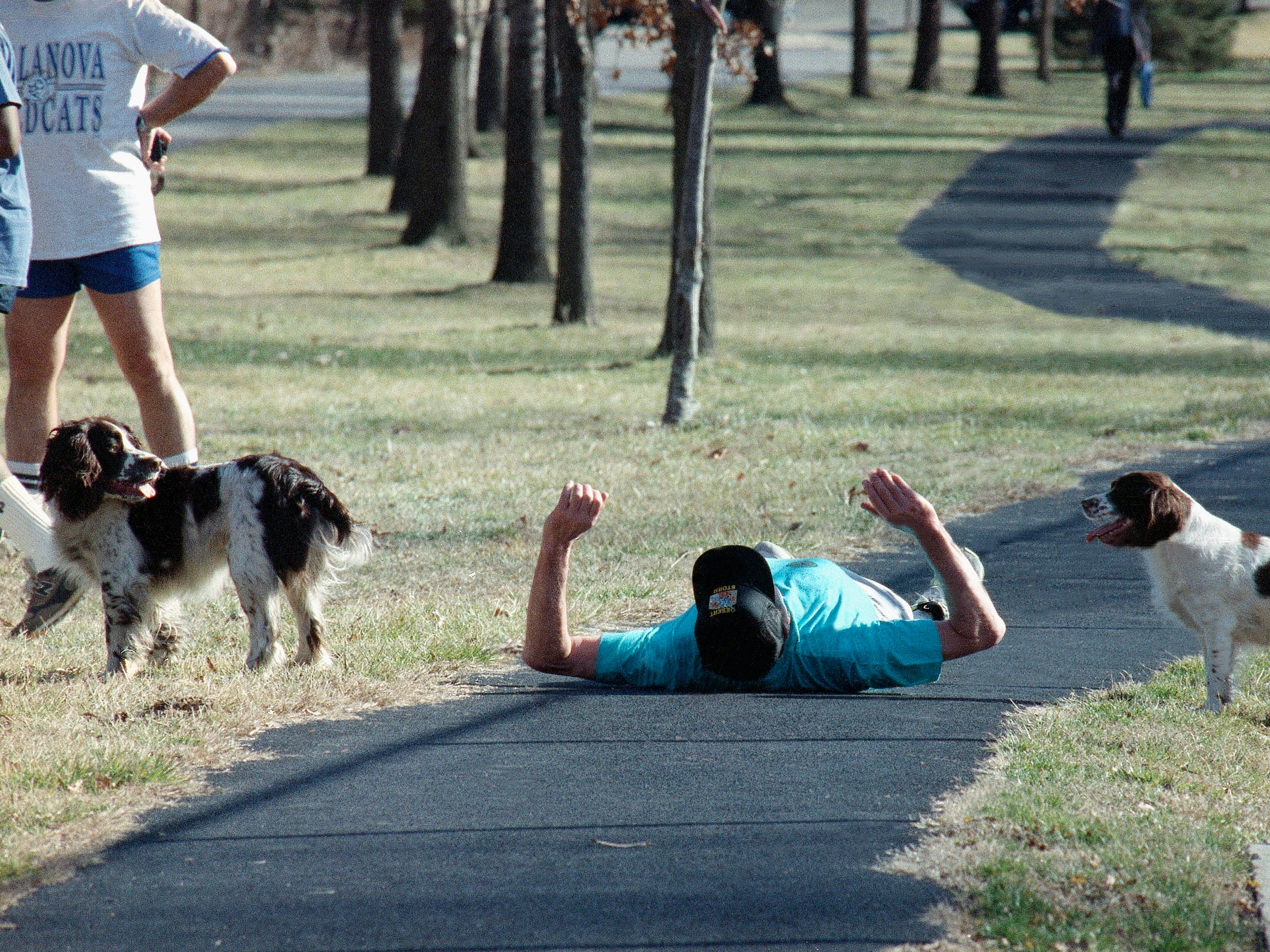 President George H.W. Bush lies on his back stretching out after jogging on Monday, Feb. 4, 1991 in Washington. Bush took his dog Ranger, left, and Millie jogging as the temperatures neared 70. (AP Photo/Dennis Cook)