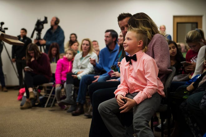 Range View Elementary School third grader Dane Best sits on the lap of his mother, Brooke Best, during a town board meeting where he presented his argument to change a law in Severance, Colo., that bans snowball fights.