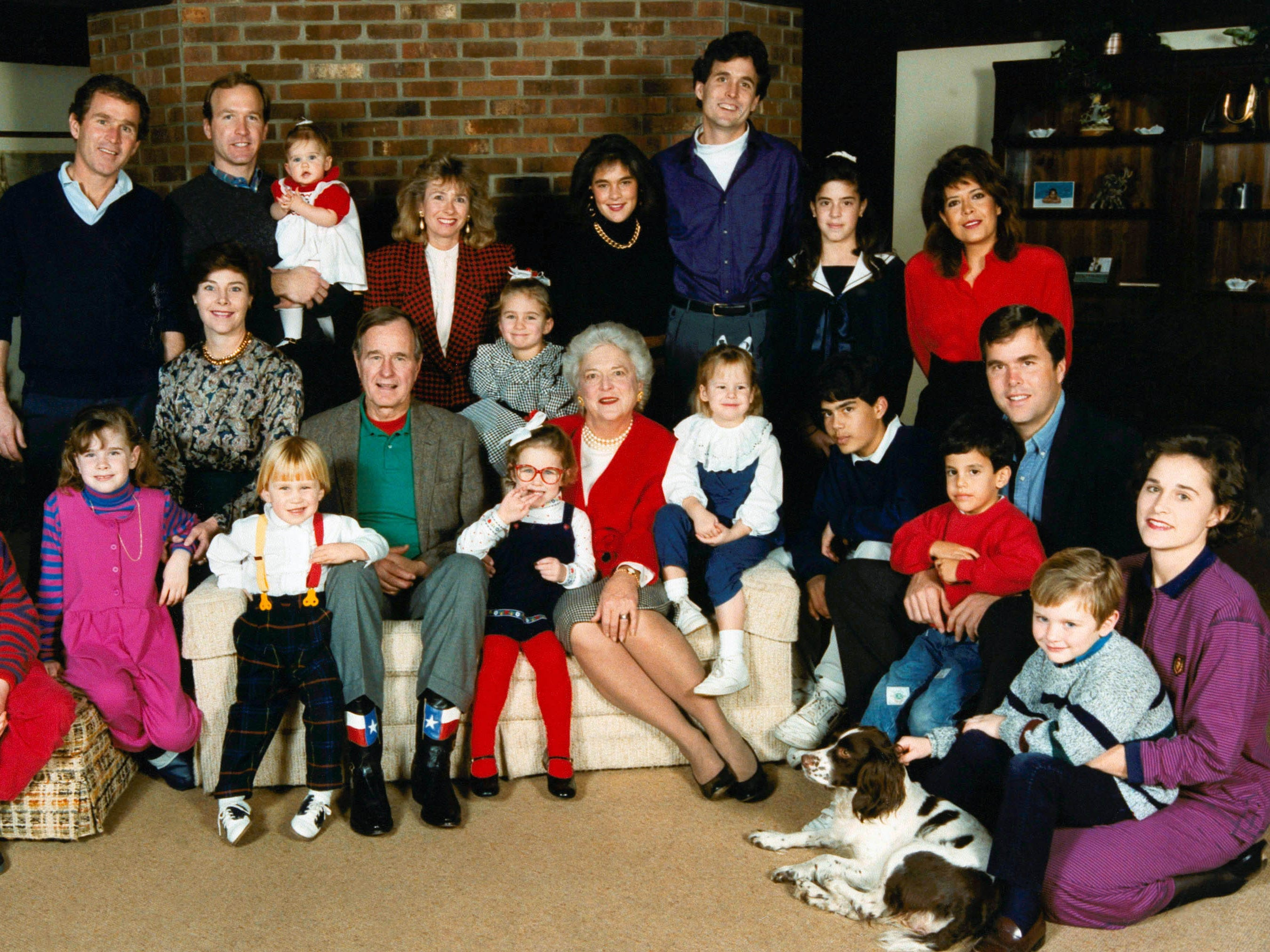 """President George H.W. Bush and his Wife, Barbara, posed for a portrait in 1989 with their children and grandchildren at Camp David, Md.  Standing at top their were their sons George W., left, and Neil Bush.    Sitting on the far right are son Jeb and daughter, Dorothy (Doro) Koch.  In front of Dorothy is Millie, a springer spaniel """"first dog.""""     (AP Photo/David Valdez/The White House)"""