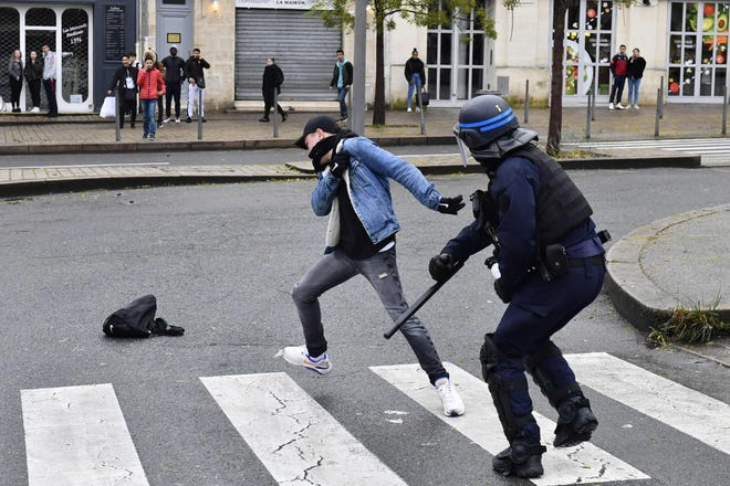 A high school student clashes with a riot police officer during a demonstration against the French government on December 3, 2018 in Bordeaux, southwestern France.