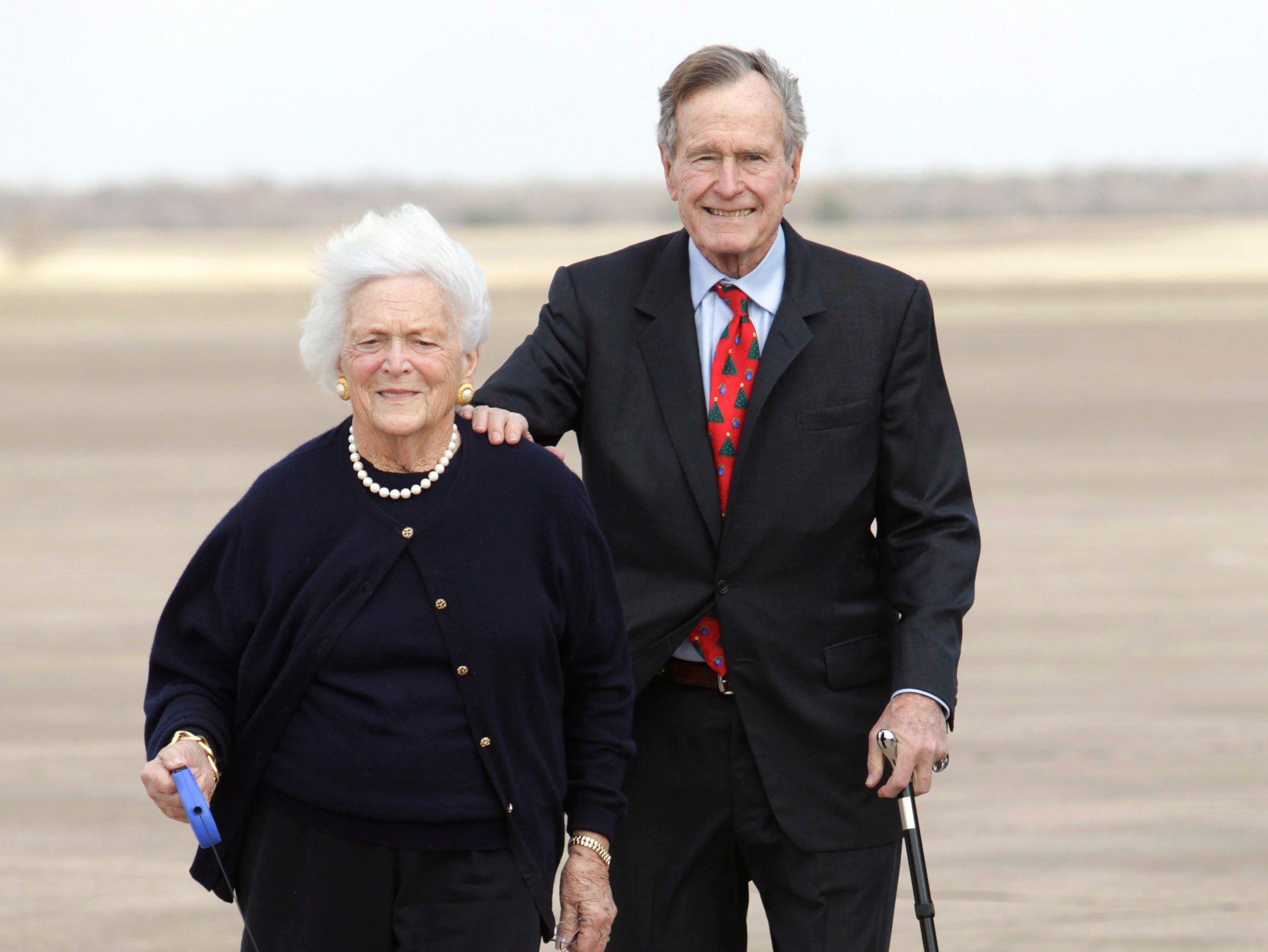 ** FILE ** In this Friday, Dec. 26, 2008 file photo, former President George H.W. Bush, right, and Barbara Bush walk their dog after arriving aboard Air Force One,  in Waco, Texas. A family spokesman said Wednesday, March 4, 2009 that former first lady Barbara Bush had successful open heart surgery. (AP Photo/Evan Vucci)