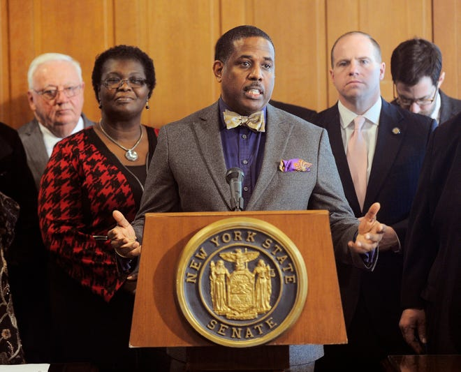 In this Feb. 6, 2017, file photo, Sen. Kevin Parker, D- Brooklyn, stands at the podium, flanked by Senate members during a news conference at the Capitol in Albany, N.Y. Parker wants to require police to scrutinize social media activity and online searches of handgun license applicants, and disqualify those who make violent or hateful posts.