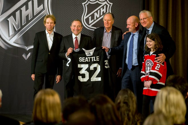 NHL commissioner Gary Bettman, center left, holds a jersey after the NHL Board of Governors announced Seattle as the league's 32nd franchise.
