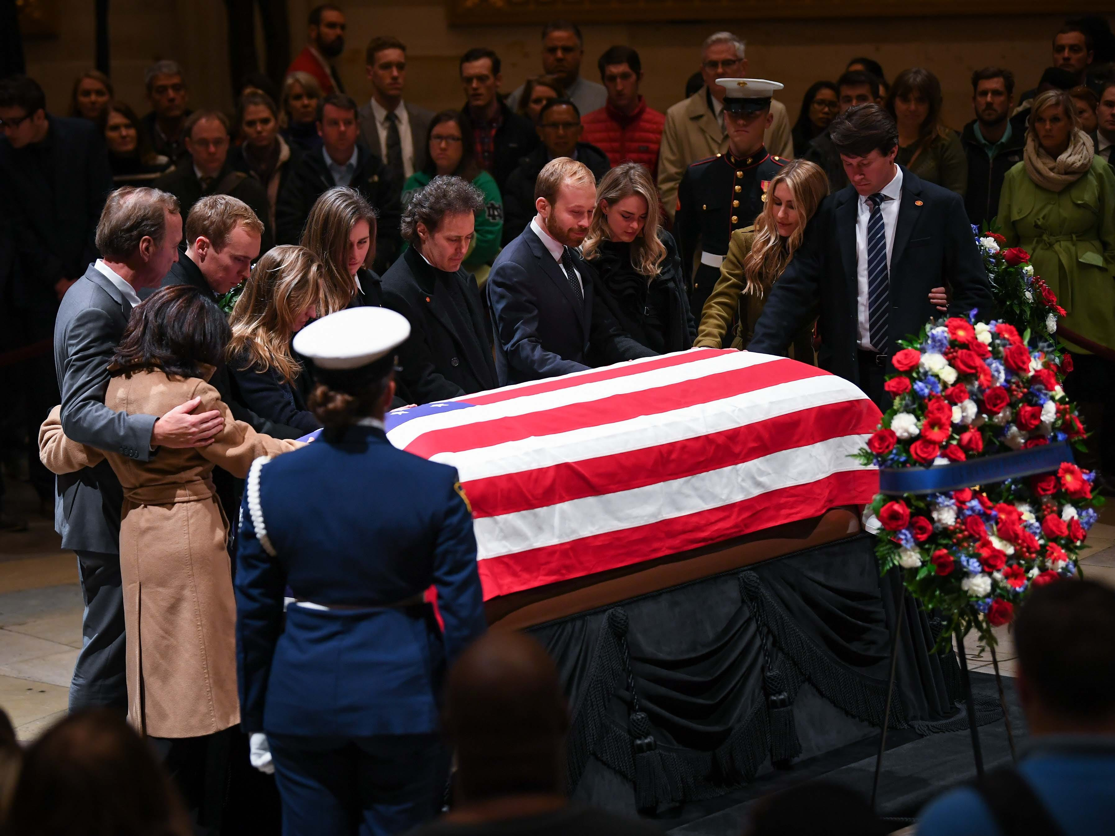 Neil Bush , left, pays his respects to his father President George H.W. Bush along with his family as the former President lies in state at the U.S. Capitol Rotunda.