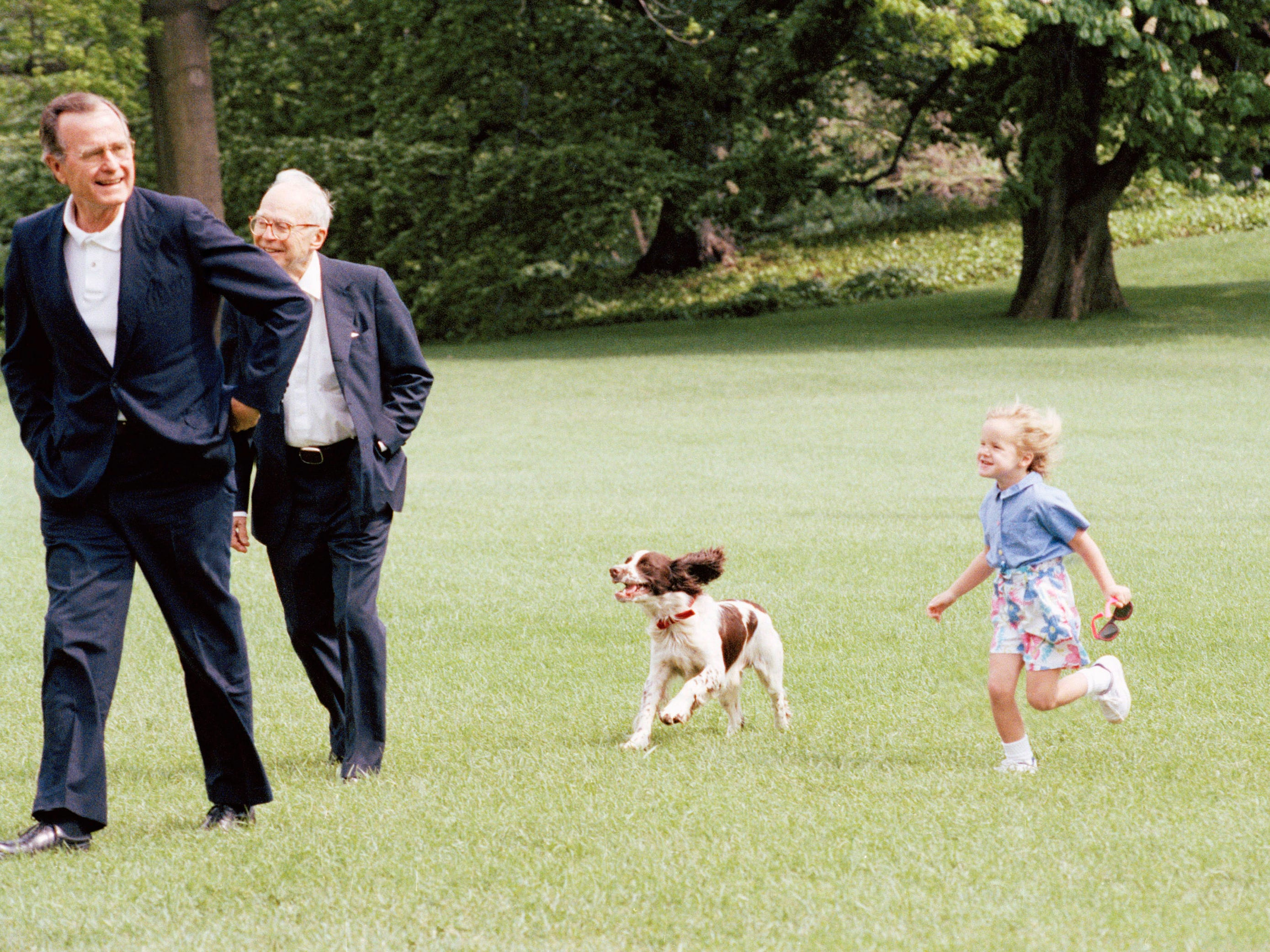 President  George H W Bush returns to the White House from Camp David, Md.    Bush is chased by granddaughter Marshall Bush and dog Ranger, an offspring of Millie.   Walker Hancock, a Texas sculptor follows the president to the White House on May 6, 1990 in Washington. (AP Photo/J. Scott Applewhite)