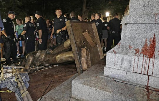 "FILE - In this Aug. 20, 2018, file photo, police stand guard after the confederate statue known as Silent Sam was toppled by protesters on campus at the University of North Carolina in Chapel Hill, N.C. Leaders of North Carolina's flagship university are meeting to decide the fate of a Confederate monument torn down by protesters. The chancellor and trustees of the University of North Carolina at Chapel Hill were finalizing a plan Monday, Dec. 3, for the century-old bronze statue known as ""Silent Sam."" (AP Photo/Gerry Broome, File)"