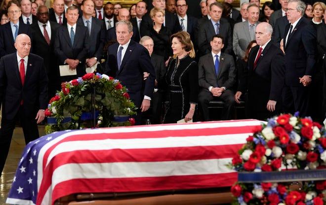 Former president George W. Bush, former first lady Laura Bush, walk past the flag draped casket of former president George H.W. Bush in the Capitol Rotunda.
