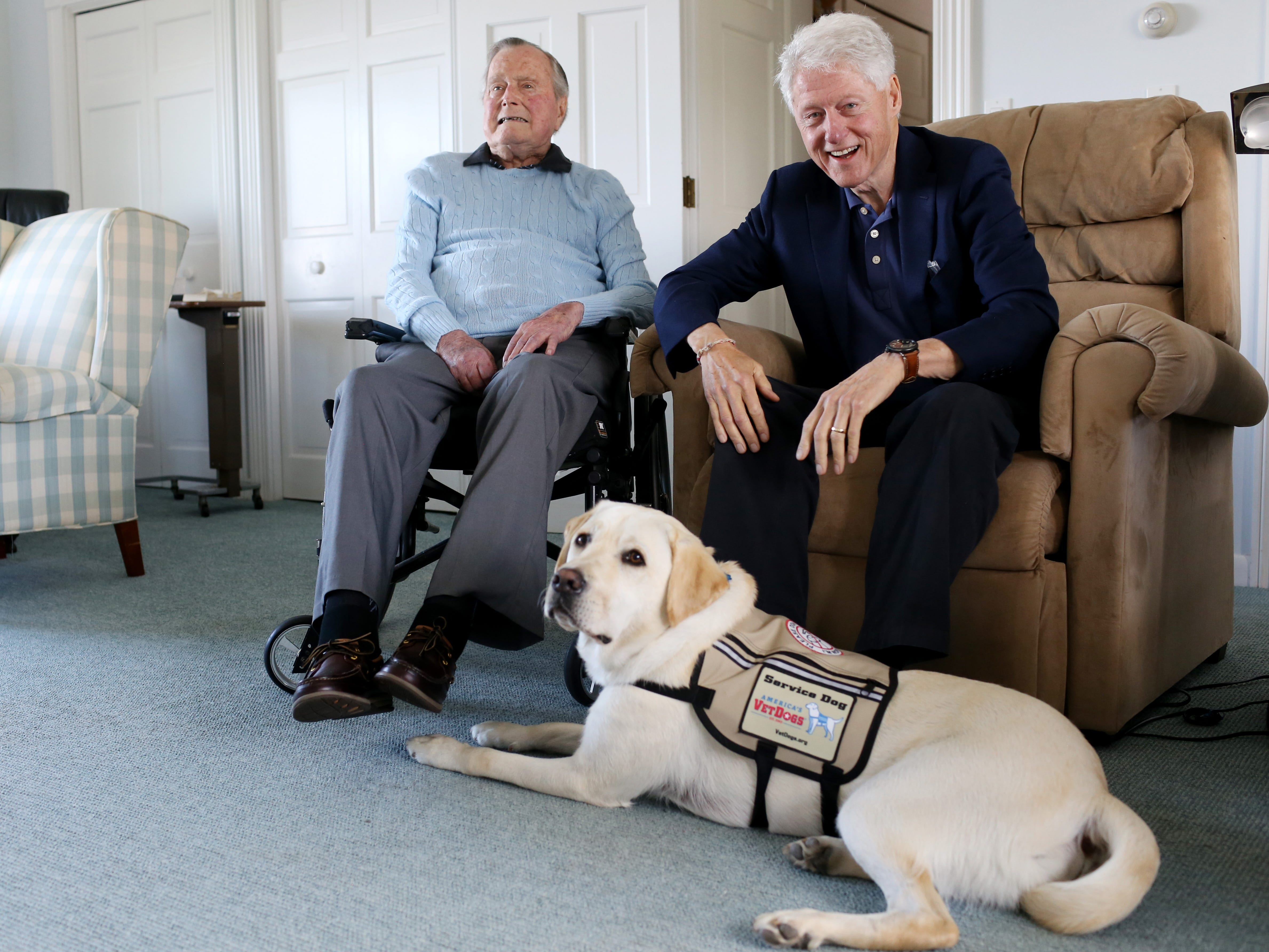 Former Republican President George H.W. Bush and former President Bill Clinton, visiting Bush, pose for a photo with Sully, June 25, 2018.