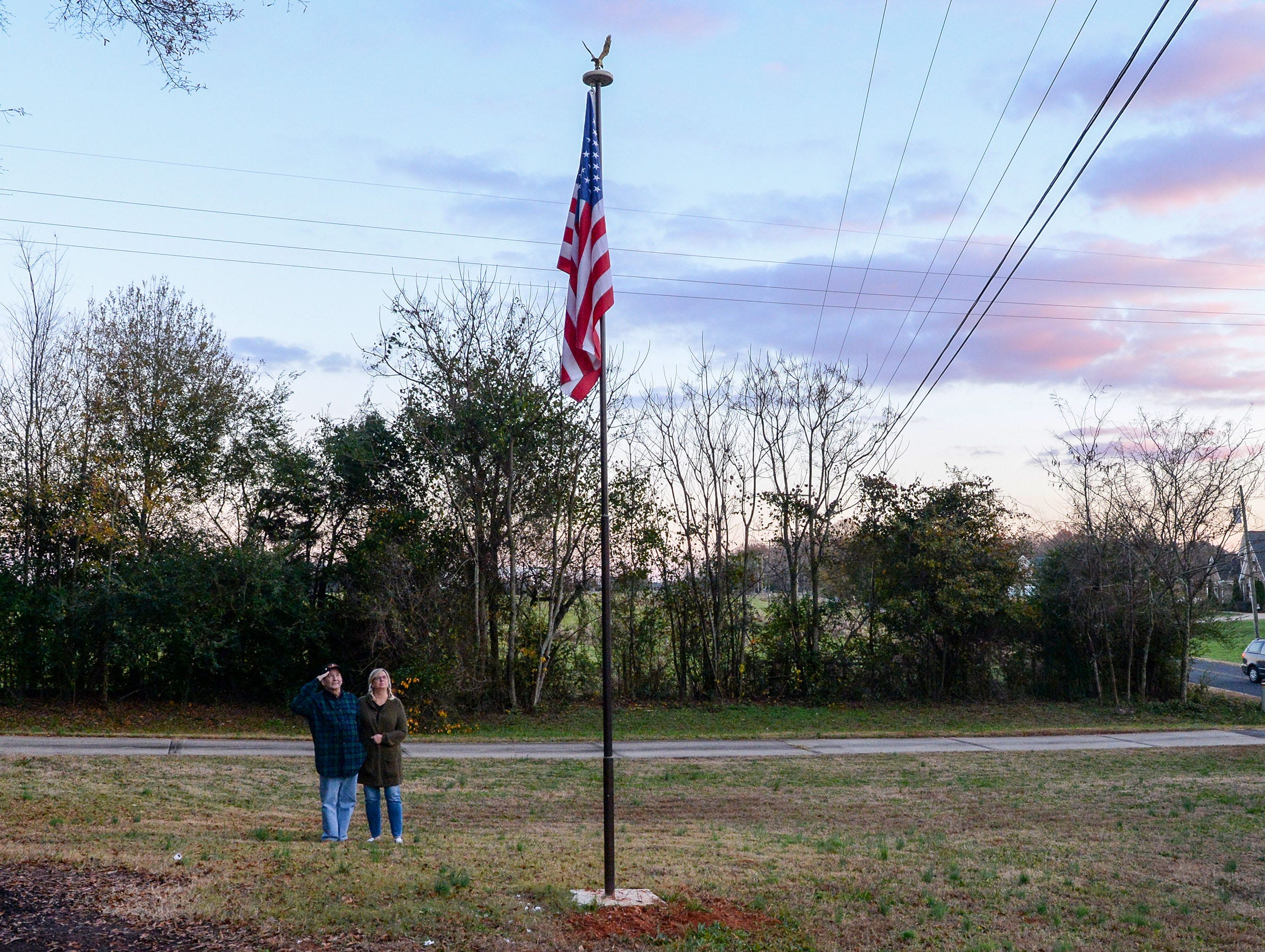Vietnam Veteran Billy Konrad, left, salutes the U.S. flag near his wife Bonnie Konrad in their front yard, between looking at the sunset sky over the West side of Anderson in December.