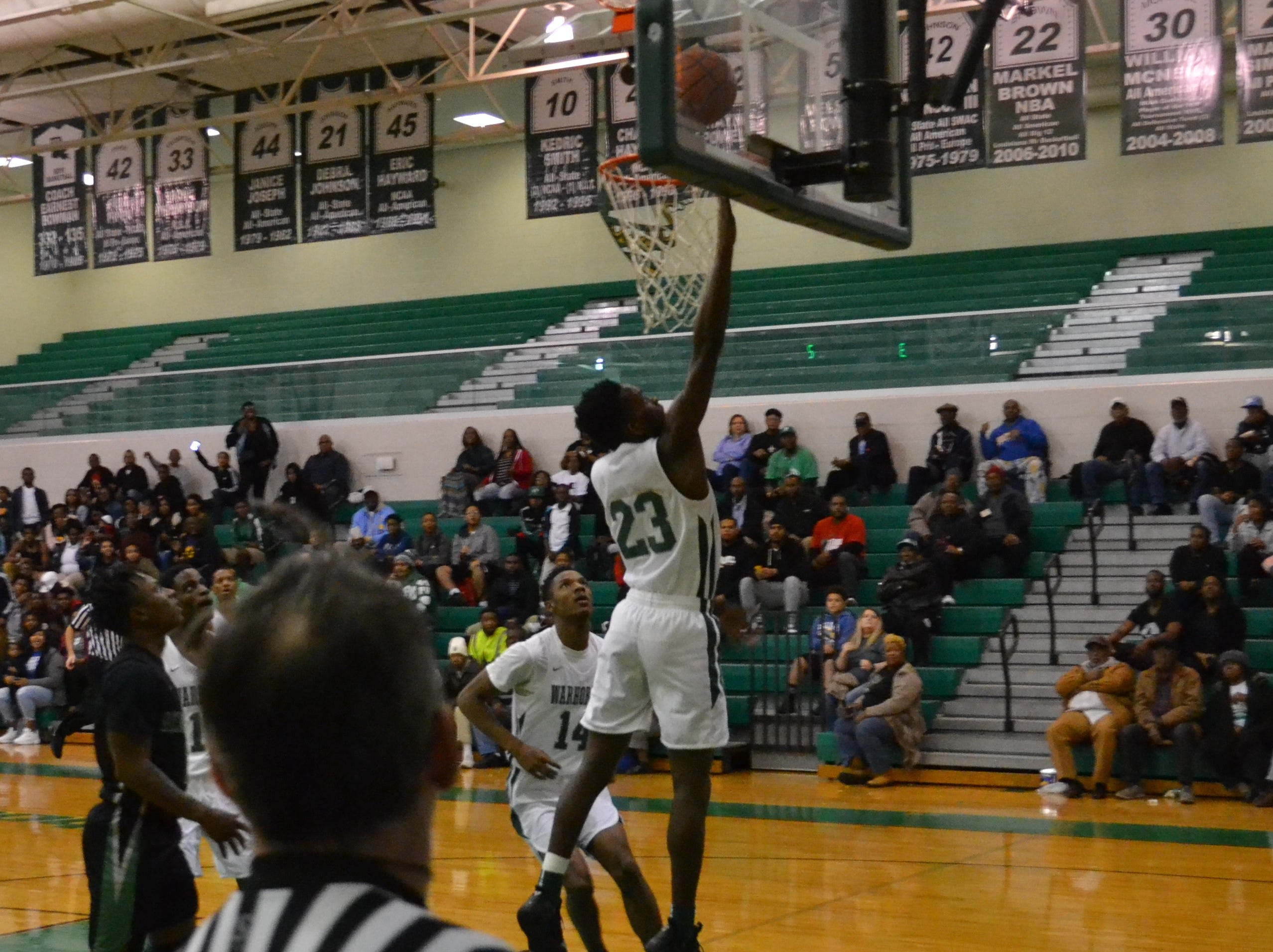 Darius Smith (23) gets a layup for the Warhorses. The Peabody boys basketball team played the Bossier Bearkats Tuesday night at the Emerald Palace. Peabody got the win 72-67.