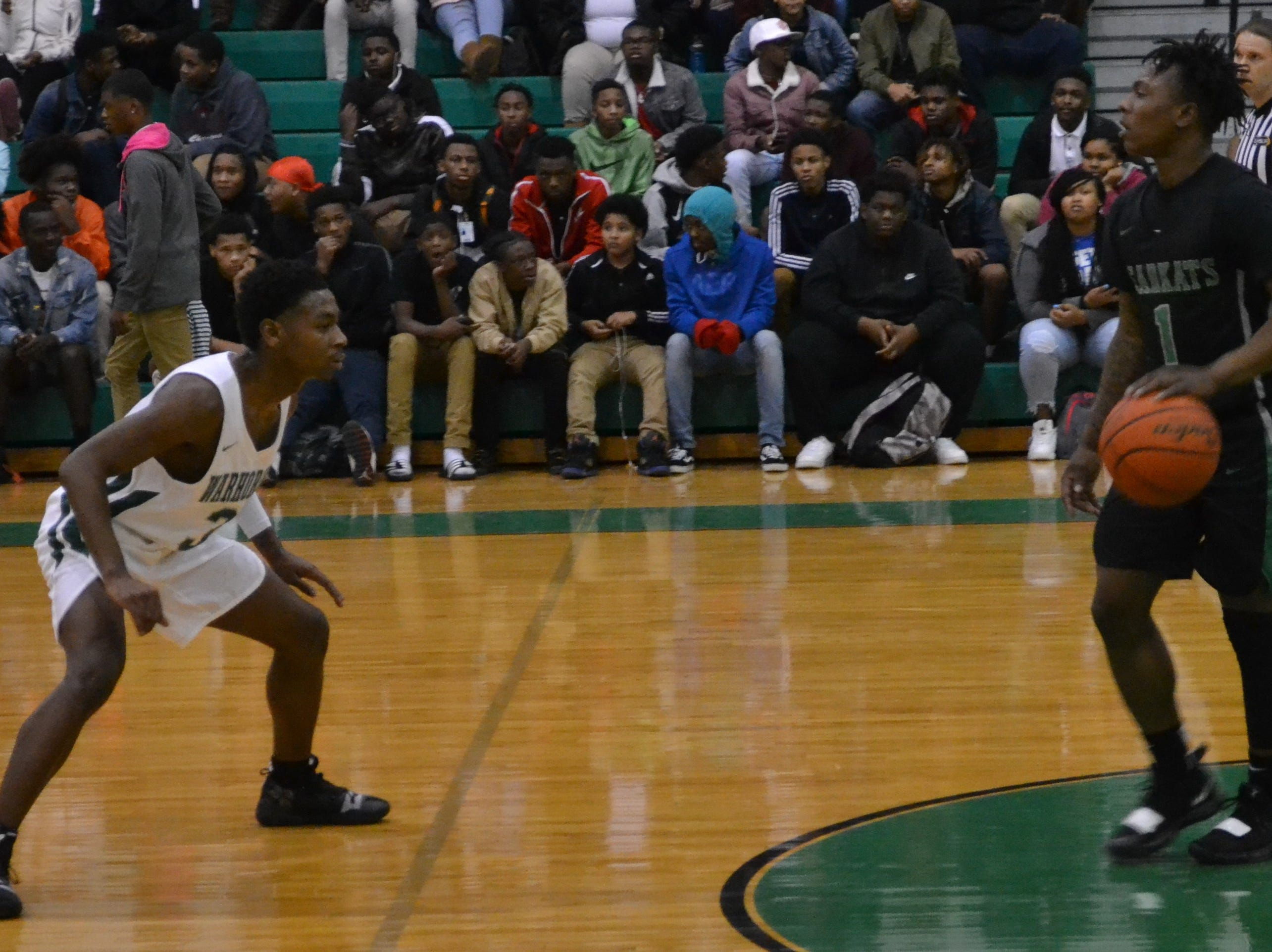 Melvion Flanagan (3) (left) defends Bossier's Jacoby Decker (1). The Peabody boys basketball team played the Bossier Bearkats Tuesday night at the Emerald Palace. Peabody got the win 72-67.