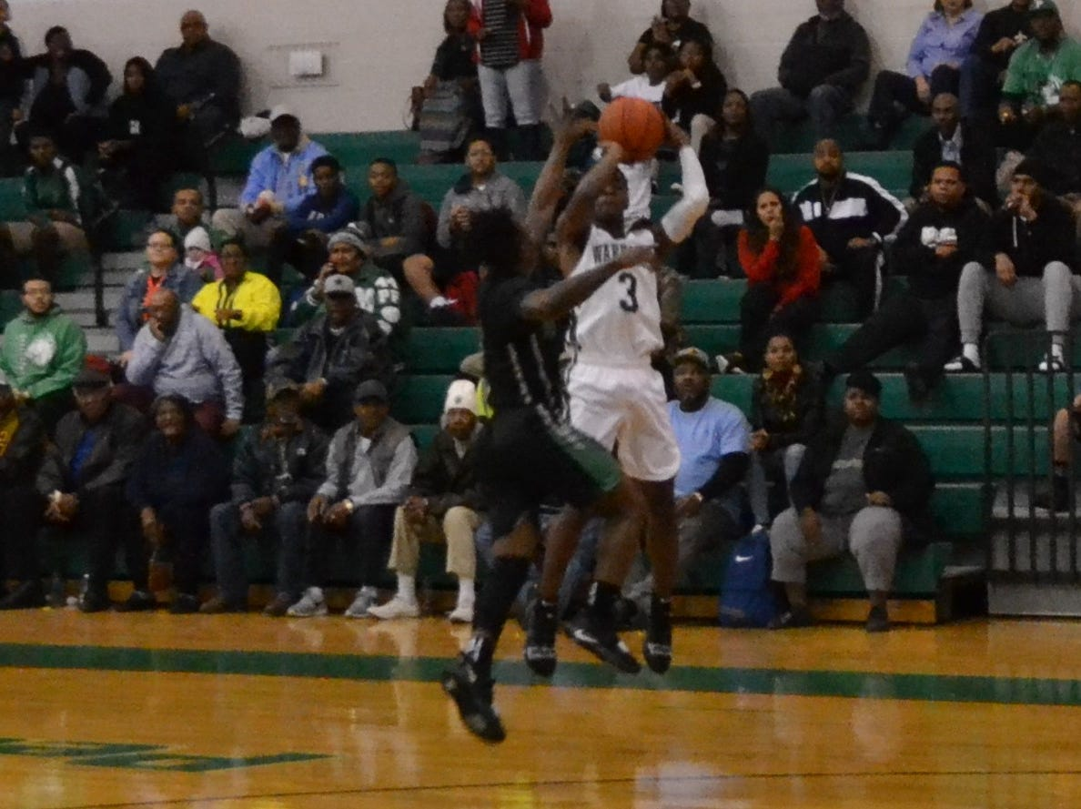 Melvion Flanagan (3) shoots a successful 3-point shot over a Bossier defender. The Peabody boys basketball team played the Bossier Bearkats Tuesday night at the Emerald Palace. Peabody got the win 72-67.