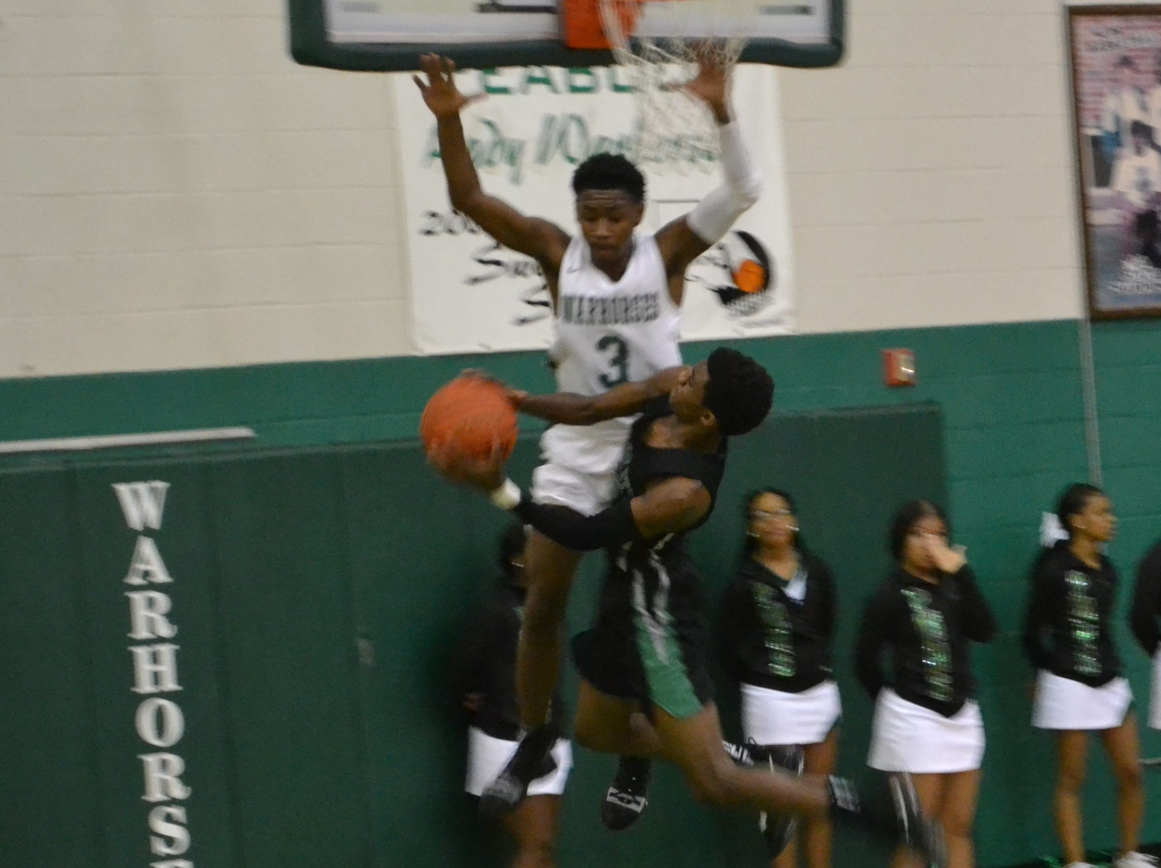 Melvion Flanagan (3) goes high to make sure Bossier's Kaalas Roots doesn't have room to shoot. The Peabody boys basketball team played the Bossier Bearkats Tuesday night at the Emerald Palace. Peabody got the win 72-67.