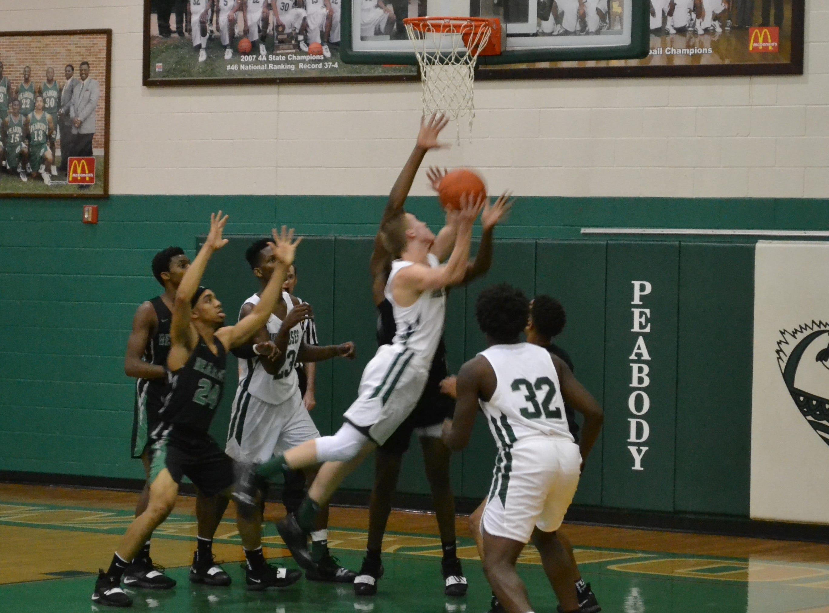 Peabody's Caleb Howe (1) struggles to get off a shot around Bossier's Dante Bell. The Peabody boys basketball team played the Bossier Bearkats Tuesday night at the Emerald Palace. Peabody got the win 72-67.
