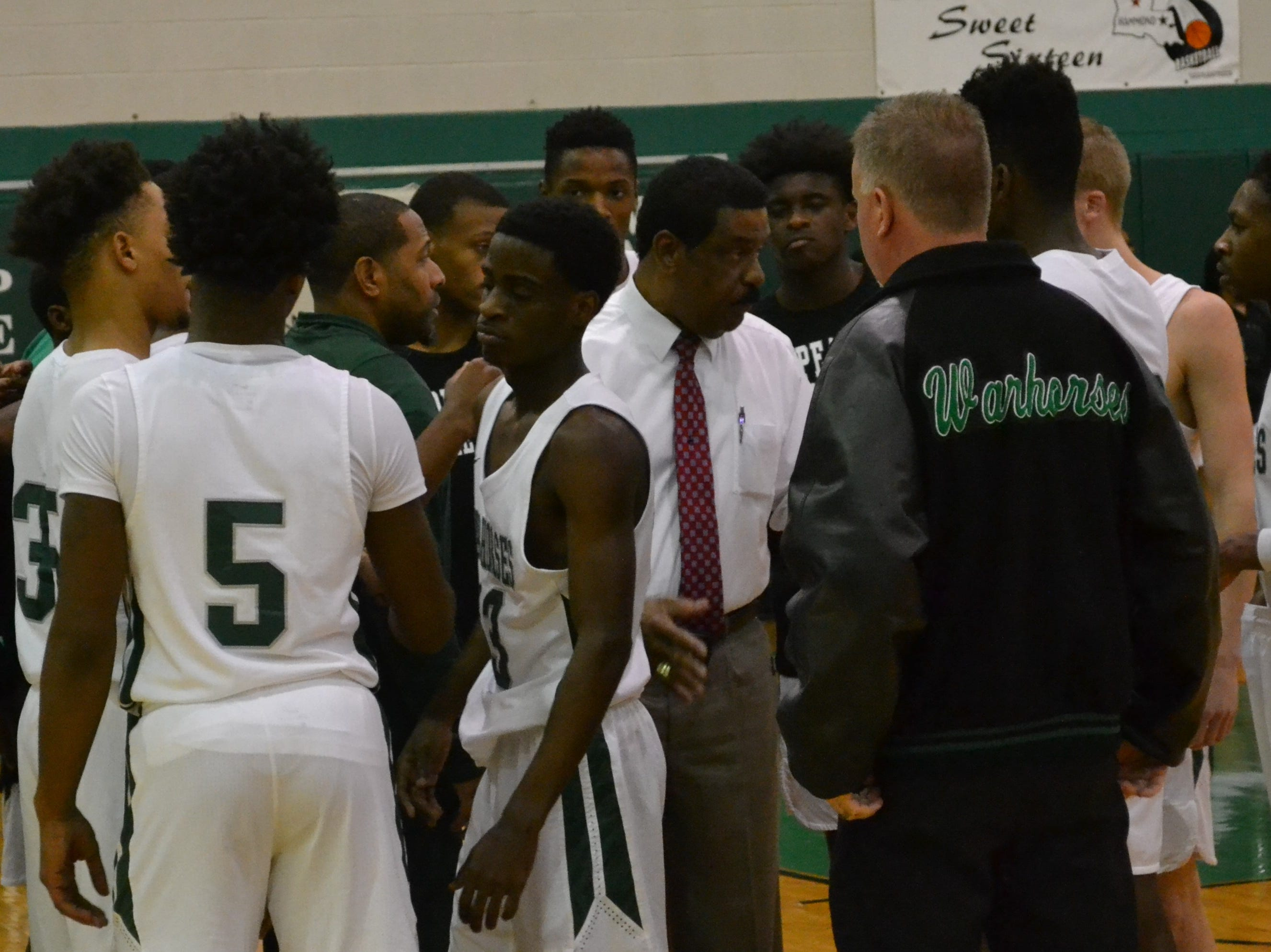 Peabody men's basketball head coach Charles Smith (center) talks with his team during a time out. The Peabody boys basketball team played the Bossier Bearkats Tuesday night at the Emerald Palace. Peabody got the win 72-67.